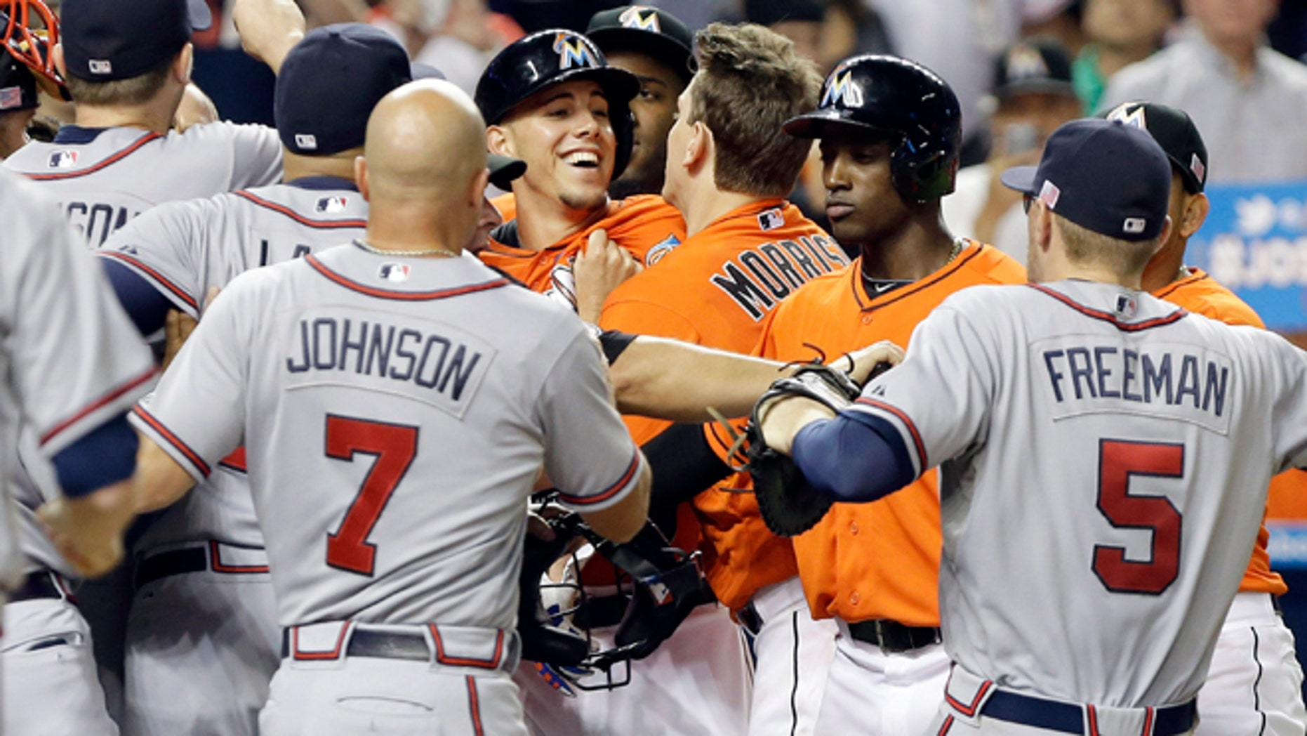 Miami Marlins starting pitcher Jose Fernandez is surrounded by Atlanta Braves players after an altercation broke out Wednesday, Sept. 11, 2013, in Miami.
