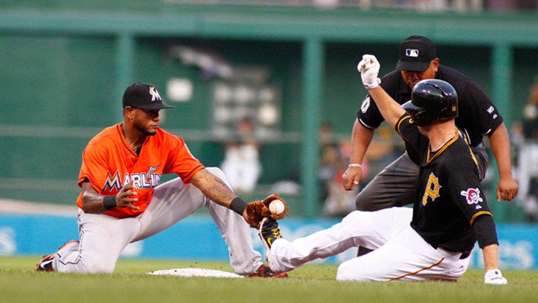PITTSBURGH, PA - AUGUST 07:  Jordy Mercer #10 of the Pittsburgh Pirates slides in safe against Jordany Valdespin #1 of the Miami Marlins during the game at PNC Park on August 7, 2014 in Pittsburgh, Pennsylvania.  (Photo by Justin K. Aller/Getty Images)