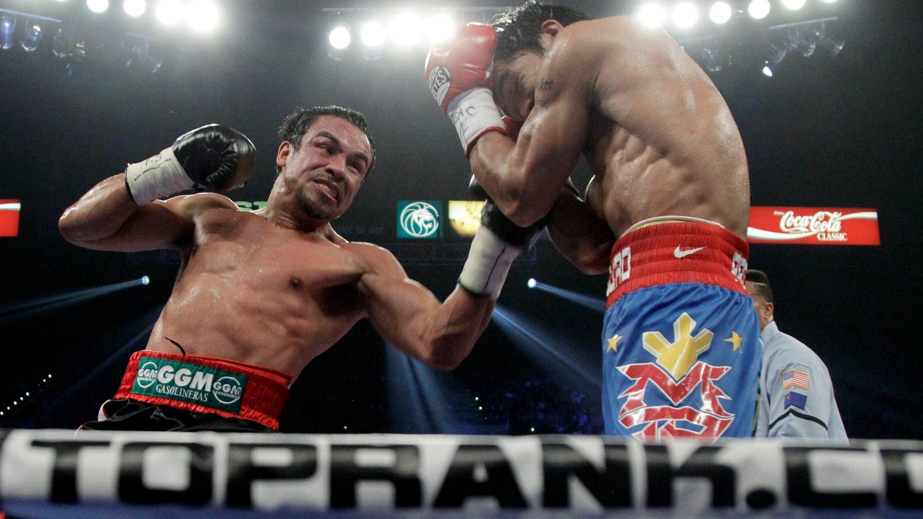 El filipino Manny Pacquiao, derecha, recibe un golpe de izquierda dal mexicano Juan Manuel Márquez durante la pelea por el título de peso welter de la OMB, el sábado 12 de noviembre de 2011, en Las Vegas. (Foto AP/Julie Jacobson)