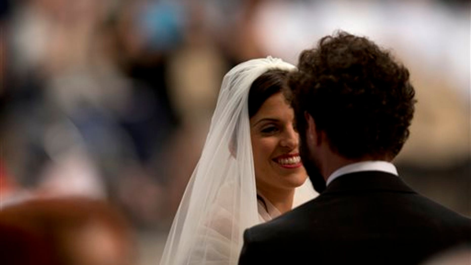 Alessandra Pucci smiles to Francesco Allotta  after being married by Pope Francis, during a wedding ceremony in St. Peter's Basilica at the Vatican, Sunday, Sept. 14, 2014.  Pope Francis married 20 couples Sunday, including some who already live together and those with children, technically a sin in the eyes of the church. (AP Photo/Alessandra Tarantino)