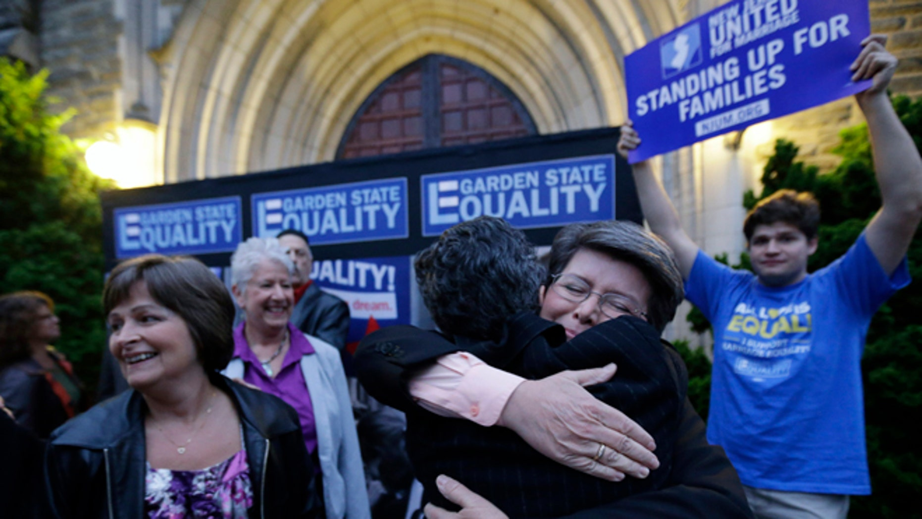 Sept. 27, 2013: Cindy Meneghin, second from right, hugs her attorney Hayley Gorenberg during a rally at Garden State Equality in Montclair, N.J., hours after a Superior Court Judge ruled that New Jersey is unconstitutionally denying federal benefits to gay couples and must allow them to marry. )