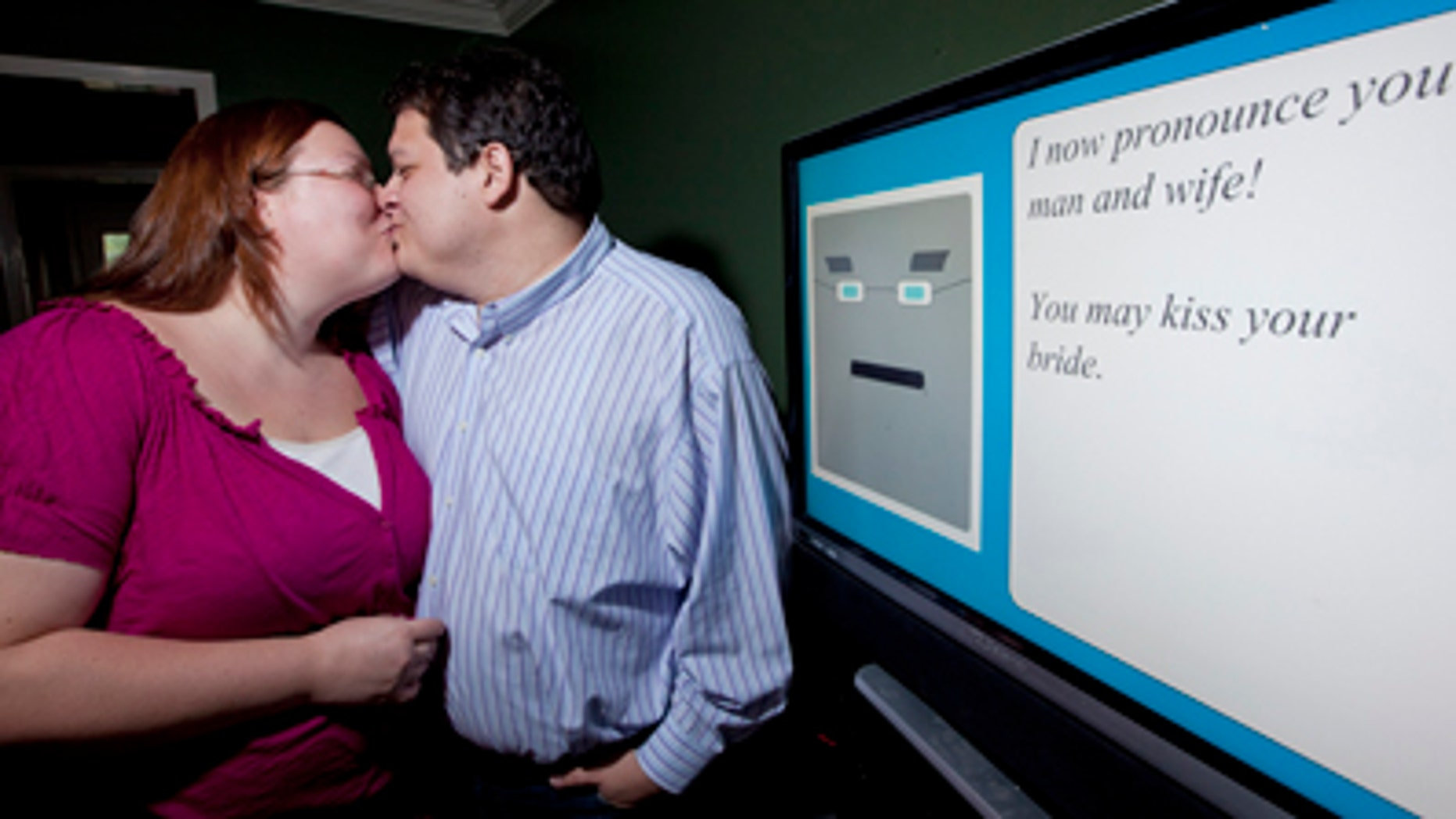 July 28, 2011: Miguel Hanson, right, kisses his fiancee Diana Wesley by the computer, in Humble, Texas. The couple couldn't get a friend to serve as the minister at their wedding, so they decided to create their own.