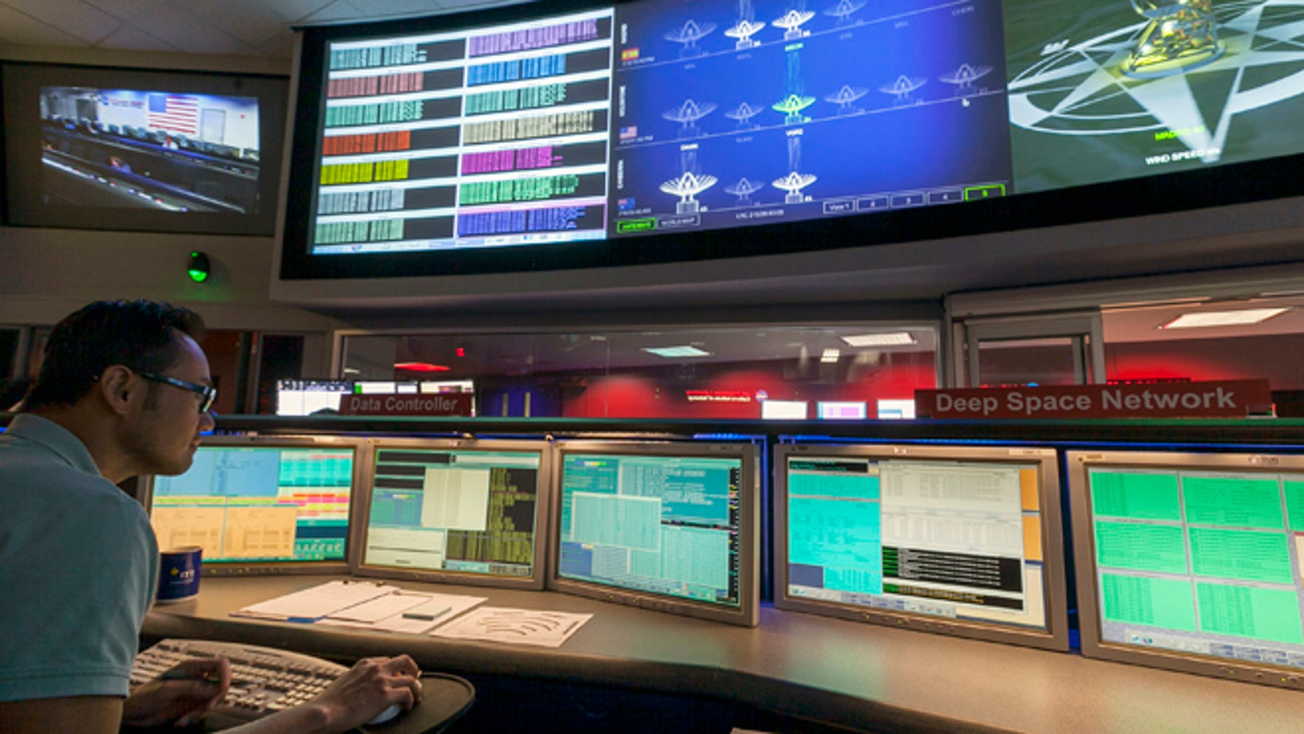 Aug. 2, 2012: This file photo shows Nick Lam, data controller, monitoring the Mars rover Curiosity from the Deep Space Network's control room at NASA's Jet Propulsion Laboratory in Pasadena, Calif.