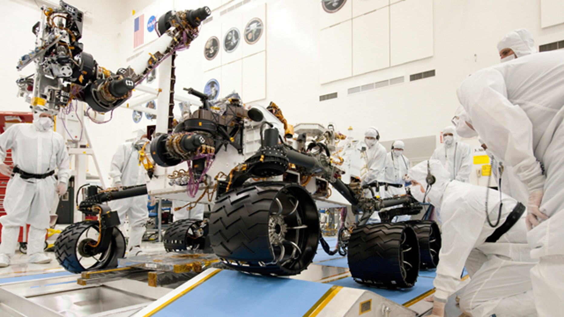 Technicians working on the new Mars rover, Curiosity. Nine months before Curiosity's scheduled launch, the space agency says the mission has burned through its reserves and needs an extra $82 million to complete testing before liftoff.