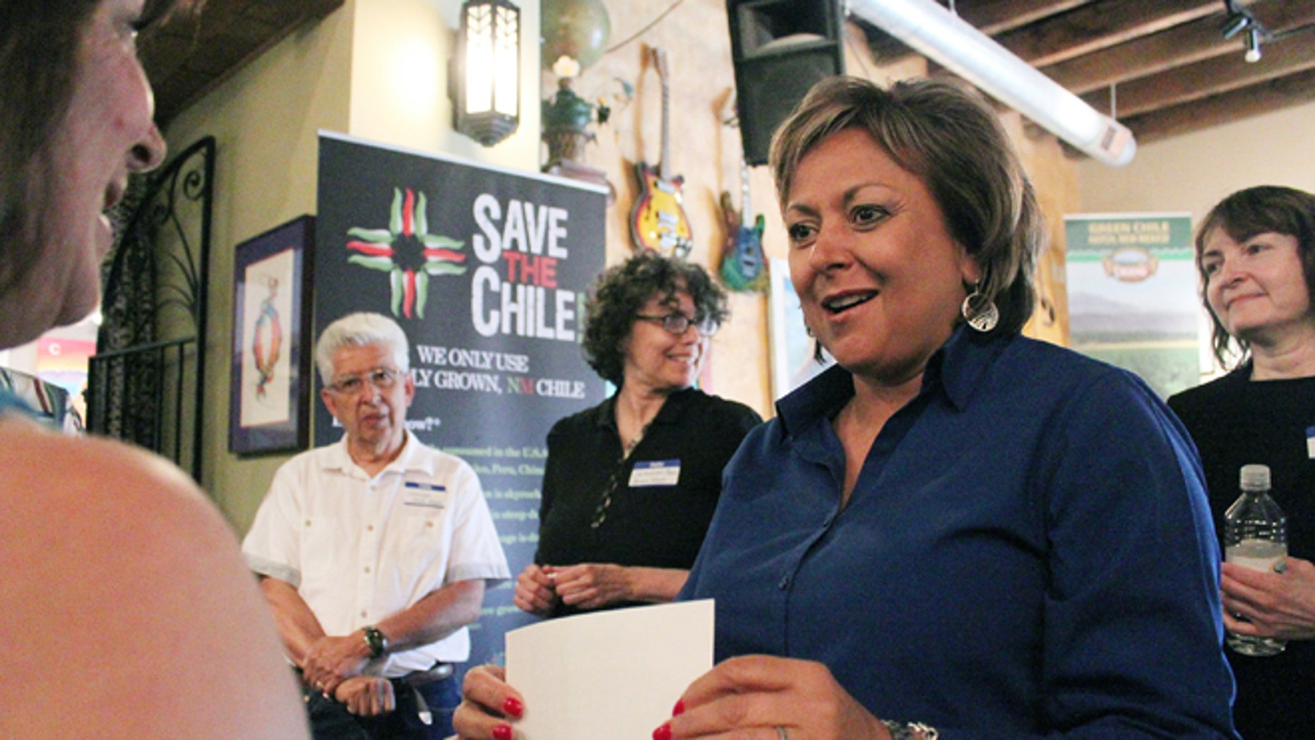 New Mexico Gov. Susana Martinez, right, talks about her love of New Mexico-grown green chile before unveiling a new certification program for the state's signature crop during at stop at The Range restaurant in Bernalillo, N.M., on Tuesday, Aug. 19, 2014. The restaurant is the first to sign up to participate in the program. (AP Photo/Susan Montoya Bryan)