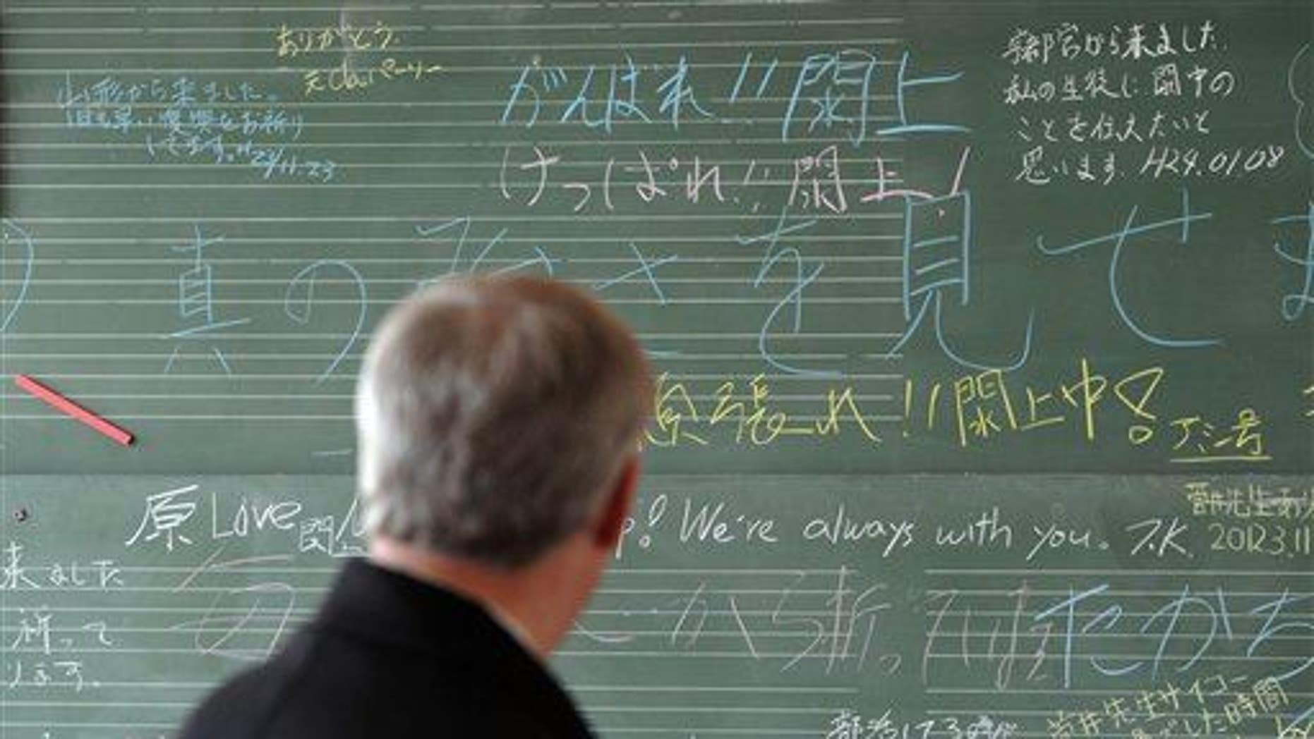 Prime Minister Stephen Harper looks at a chalk board filled with well wishes at the Yuriage Junior High School as he visits the coastal region of Japan, near Sendai, on Monday, March 26, 2012.