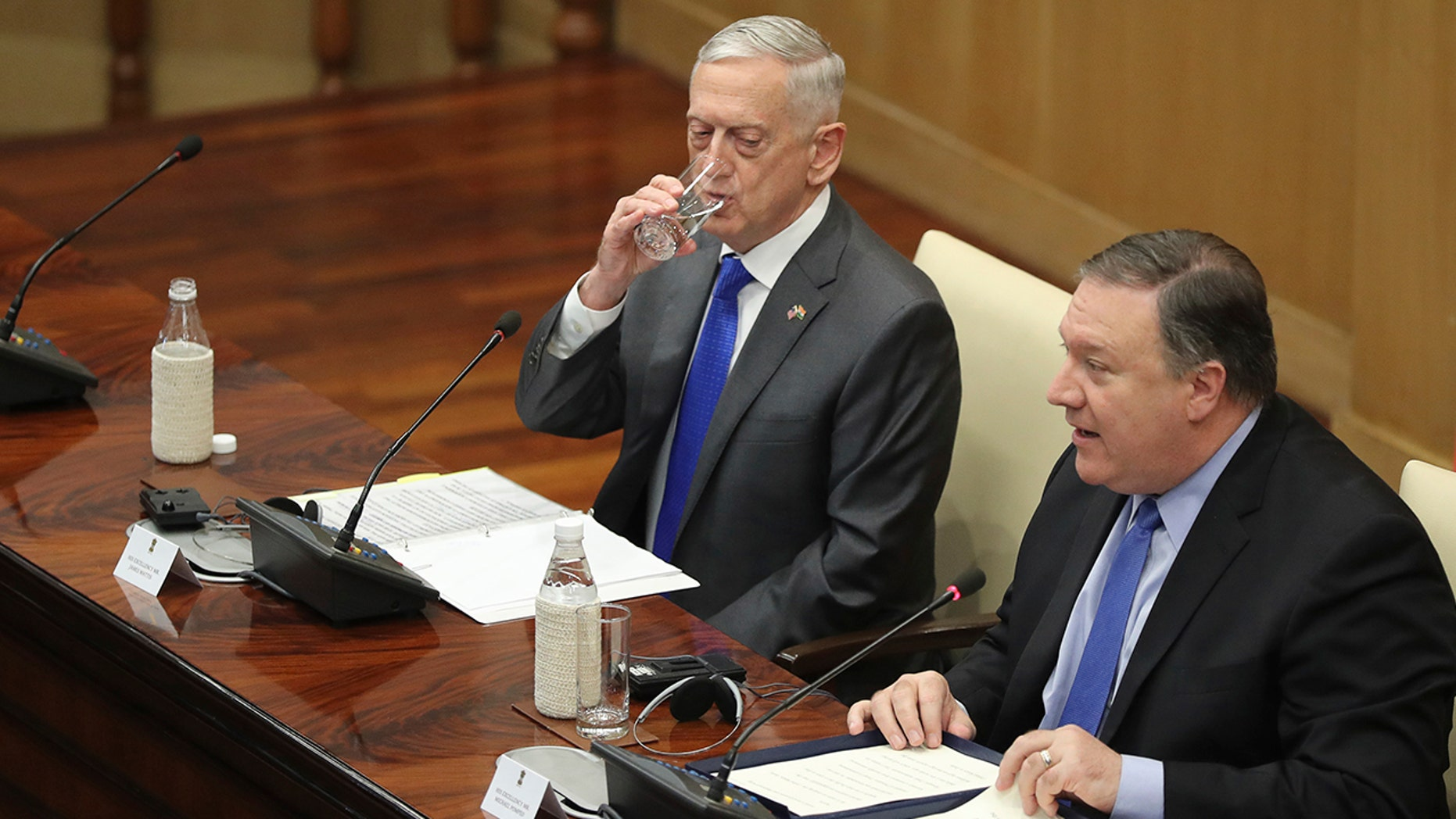U.S. Defense Secretary James Mattis, left, drinks water as U.S. Secretary of State Mike Pompeo, makes his statement after meeting in New Delhi, India, Thursday with Indian officials.