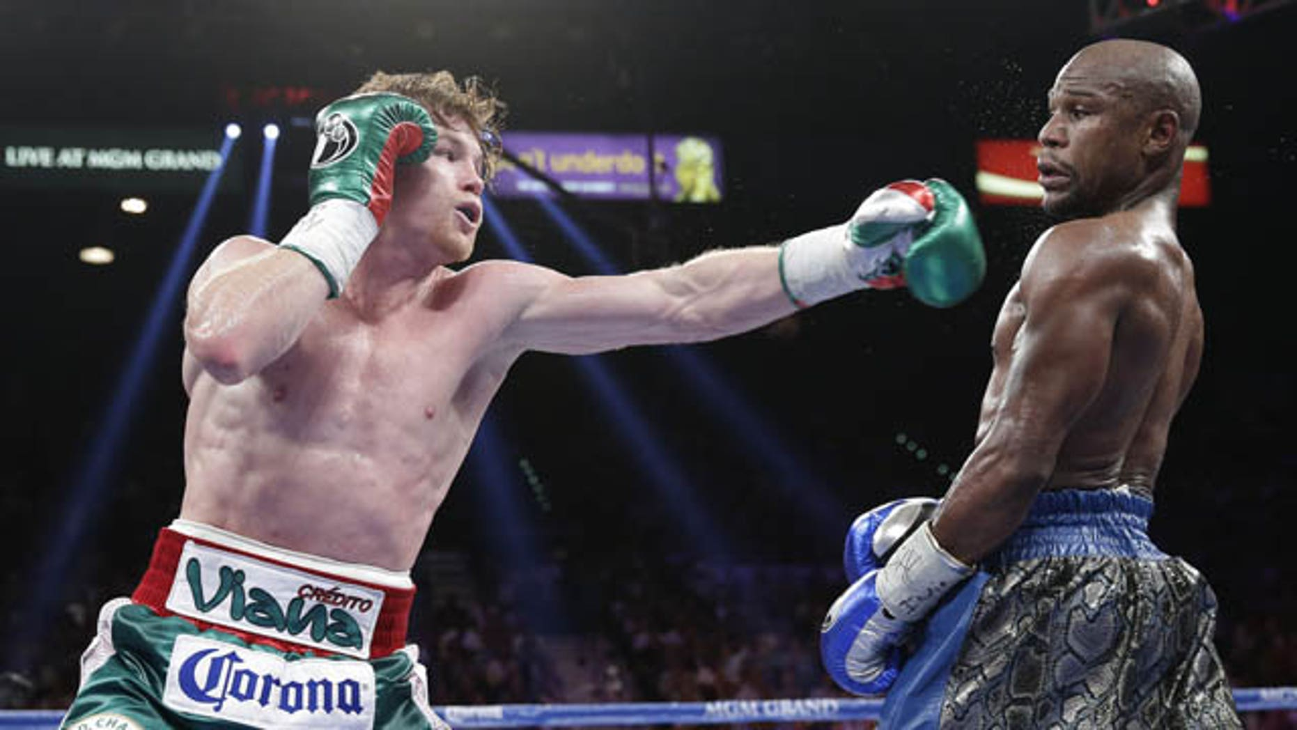 September 14, 2013: Canelo Alvarez throws a jab at Floyd Mayweather Jr. during a 152-pound title fight in Las Vegas. (AP Photo)