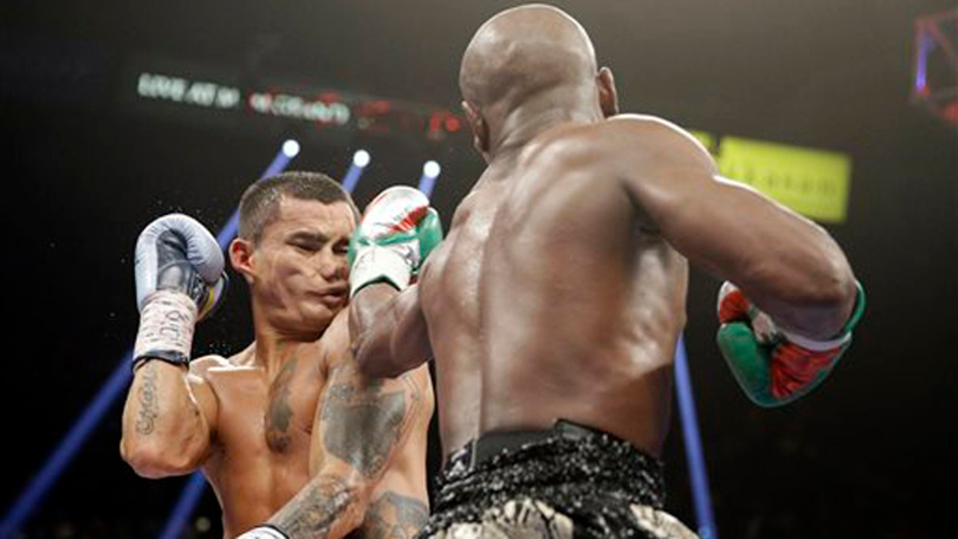 Floyd Mayweather punches Marcos Maidana, left, during their title boxing bout Saturday, Sept. 13, 2014, in Las Vegas. (AP Photo/John Locher)