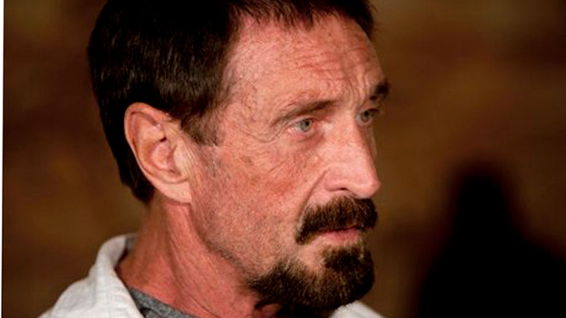 "Software company founder John McAfee listens to a question during an interview at a local restaurant in Guatemala City, Tuesday, Dec. 4, 2012.  McAfee, 67, has been identified as a ""person of interest"" in the killing of his neighbor in Belize, 52-year-old Gregory Faull. Police are urging McAfee to come in for questioning. The anti-virus company founder fled Belize and is seeking political asylum in Guatemala, according to his lawyer Telesforo Guerra. (AP Photo/Moises Castillo)"
