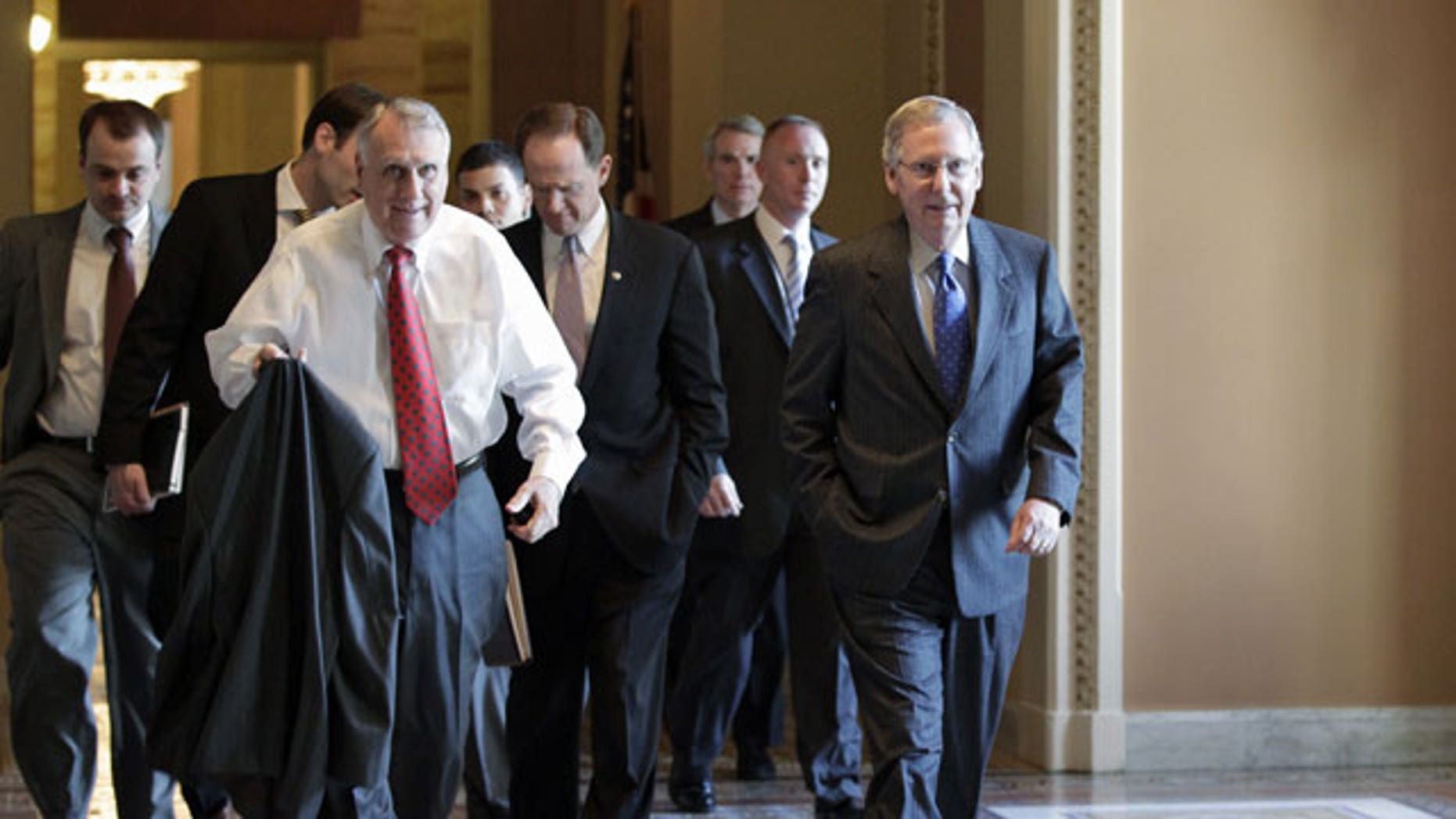 November 3, 2011: Senate Minority Leader Mitch McConnell of Ky., right, walks to the floor of the Senate with Senate Minority Whip Jon Kyl of Ariz., left, Sen. Patrick Toomey, R-Pa., center, and others, on Capitol Hill in Washington.
