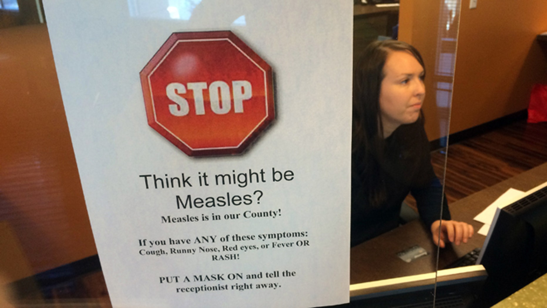FILE - In this Feb. 7, 2015, file photo, a sign warns of the dangers of measles in the reception area of a pediatrician's office in Scottsdale, Ariz., Saturday, Feb. 7, 2015. Arizona officials are threatening legal action against an immigration detention center south of Phoenix where an outbreak of measles has affected 22 this year, Thursday, July 7, 2016. (AP Photo/Tom Stathis, File)