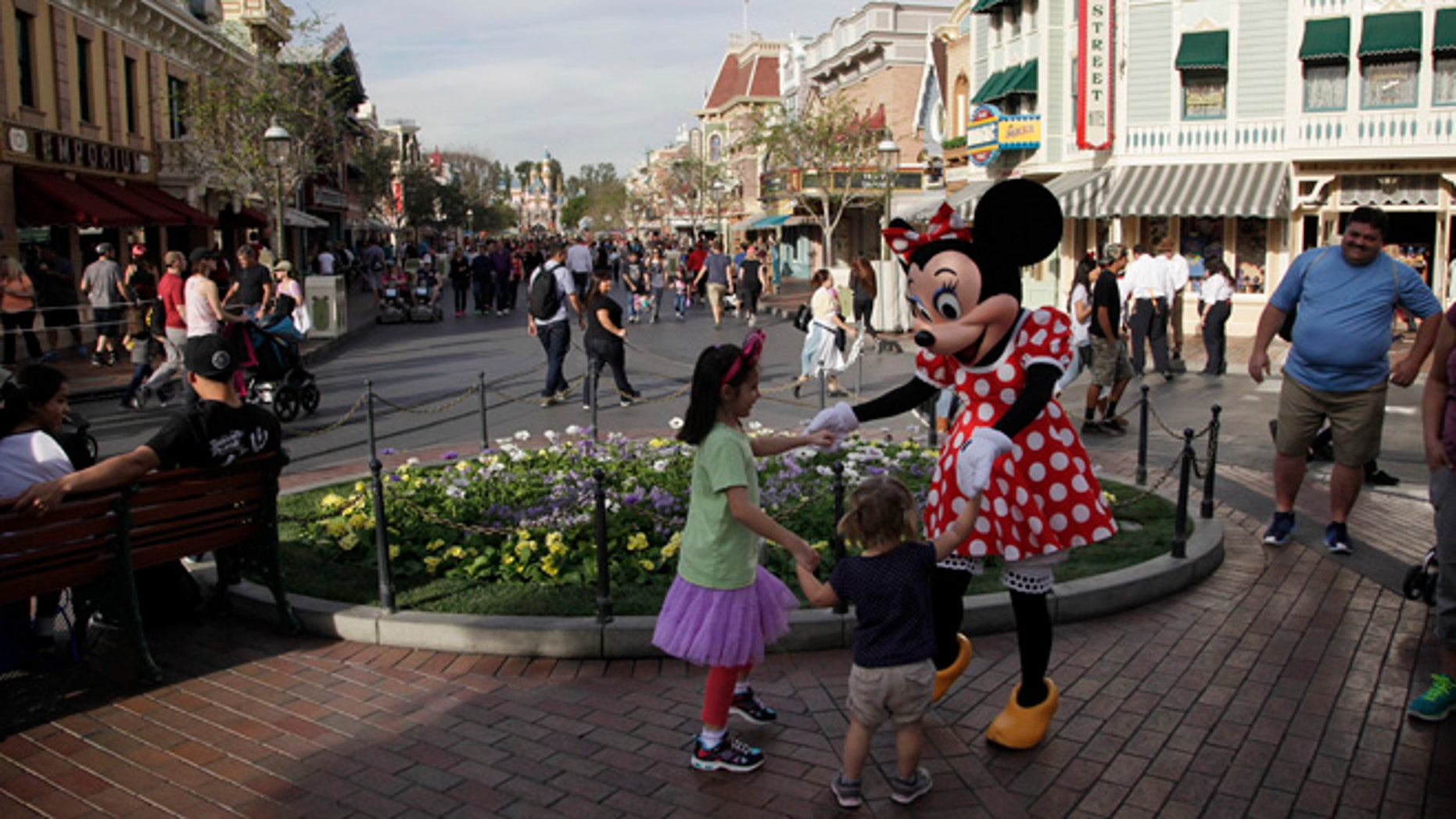 Minnie Mouse dances with visitors at Disneyland, Thursday, Jan. 22, 2015, in Anaheim, Calif. A major measles outbreak traced to Disneyland has brought criticism down on the small but vocal movement among parents to opt out of vaccinations for their children. (AP Photo/Jae C. Hong)