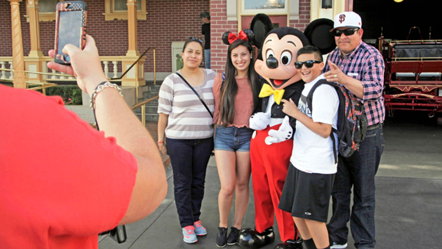Visitors pose with Mickey Mouse at Disneyland in Anaheim, Calif.