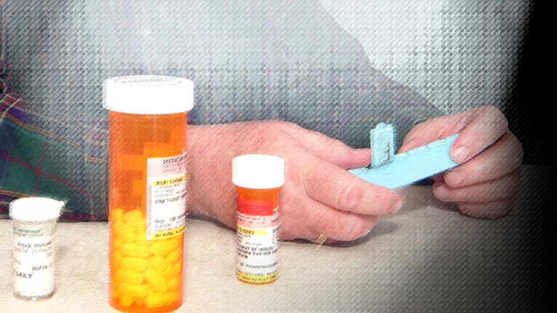 Don Brock of Litchfield, Minn., looks at some of his prescription drugs at his home in Litchfield, Minn. Friday, Feb. 10, 2006. Brock quit buying prescription drugs from Canada this year, now that he's signed up for the new federal Medicare drug benefit. (AP Photo/Bill Zimmer)