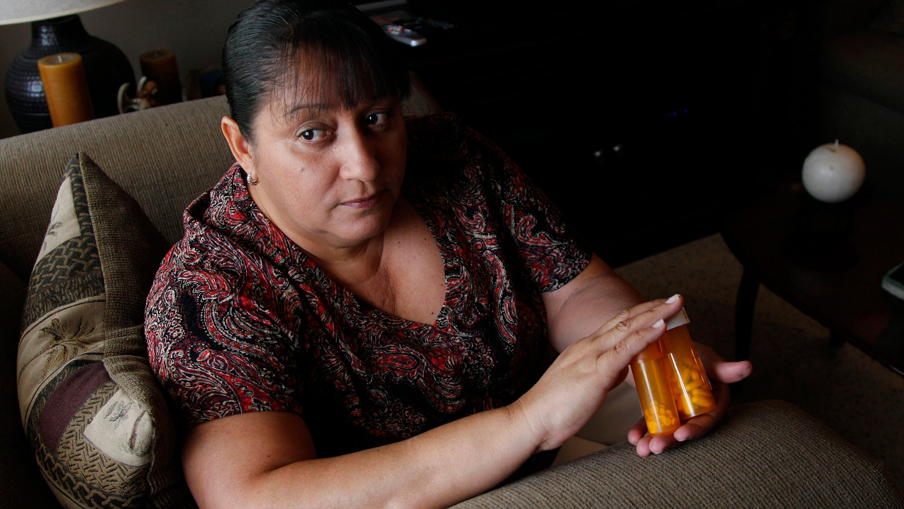 Sandra Pico, 52,  holds medications she takes, at her home in North Miami Beach, Fla. Pico makes about $15,000 a year working about 20 hours a week as a home health aide, a bit too much to qualify for Medicaid.