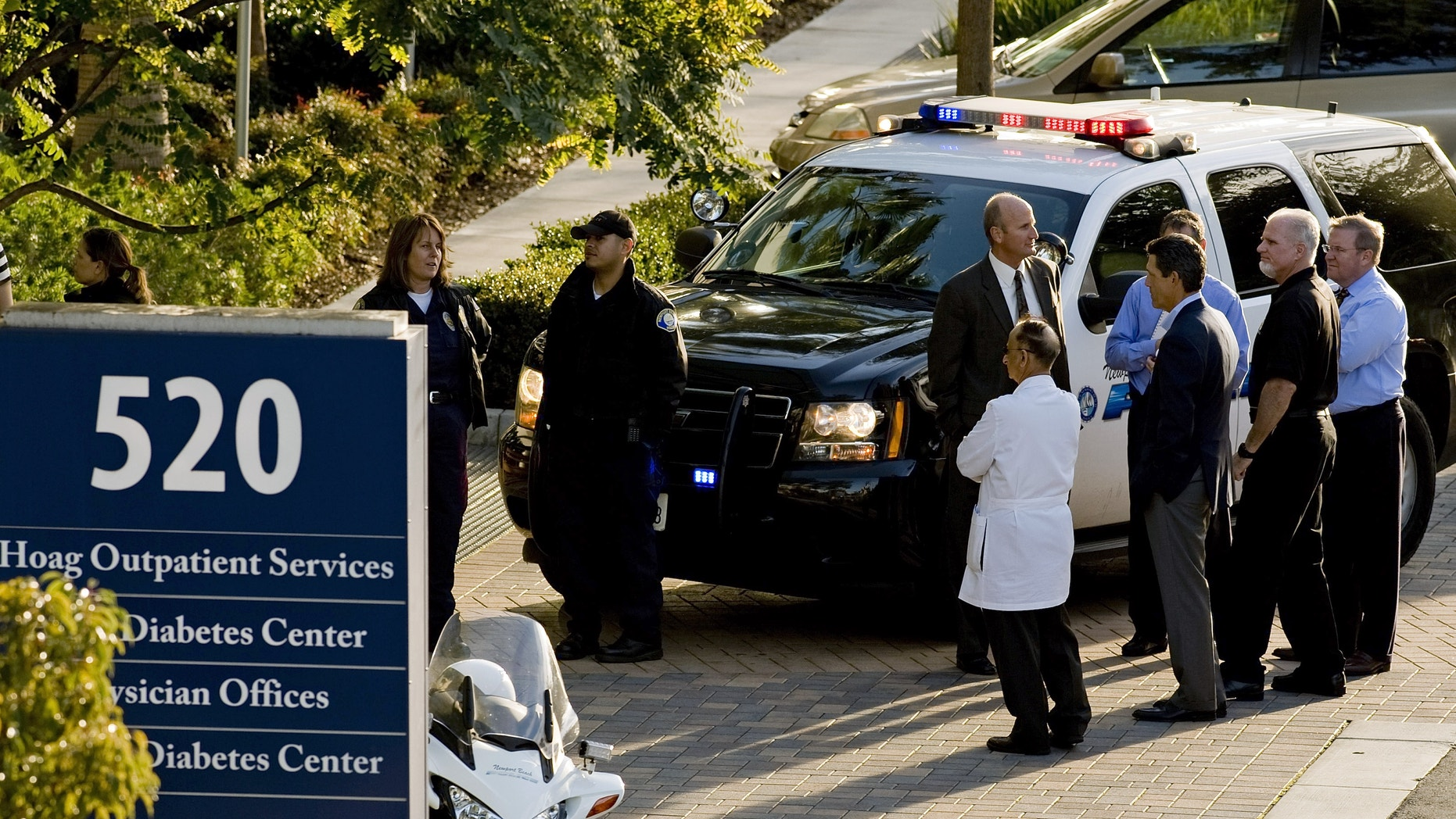 28, 2013: Police and medical personnel stand outside a medical office near