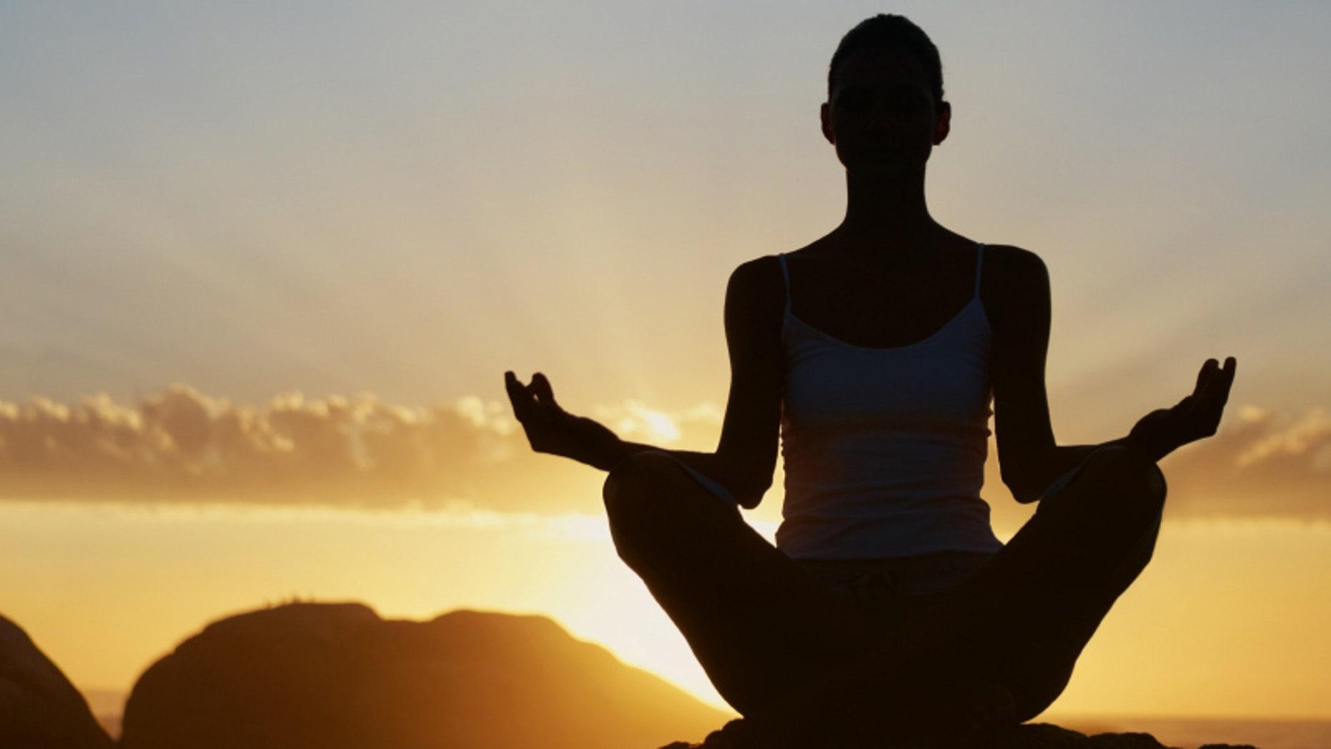 Beautiful silhouette woman sitting in lotus pose at sunset