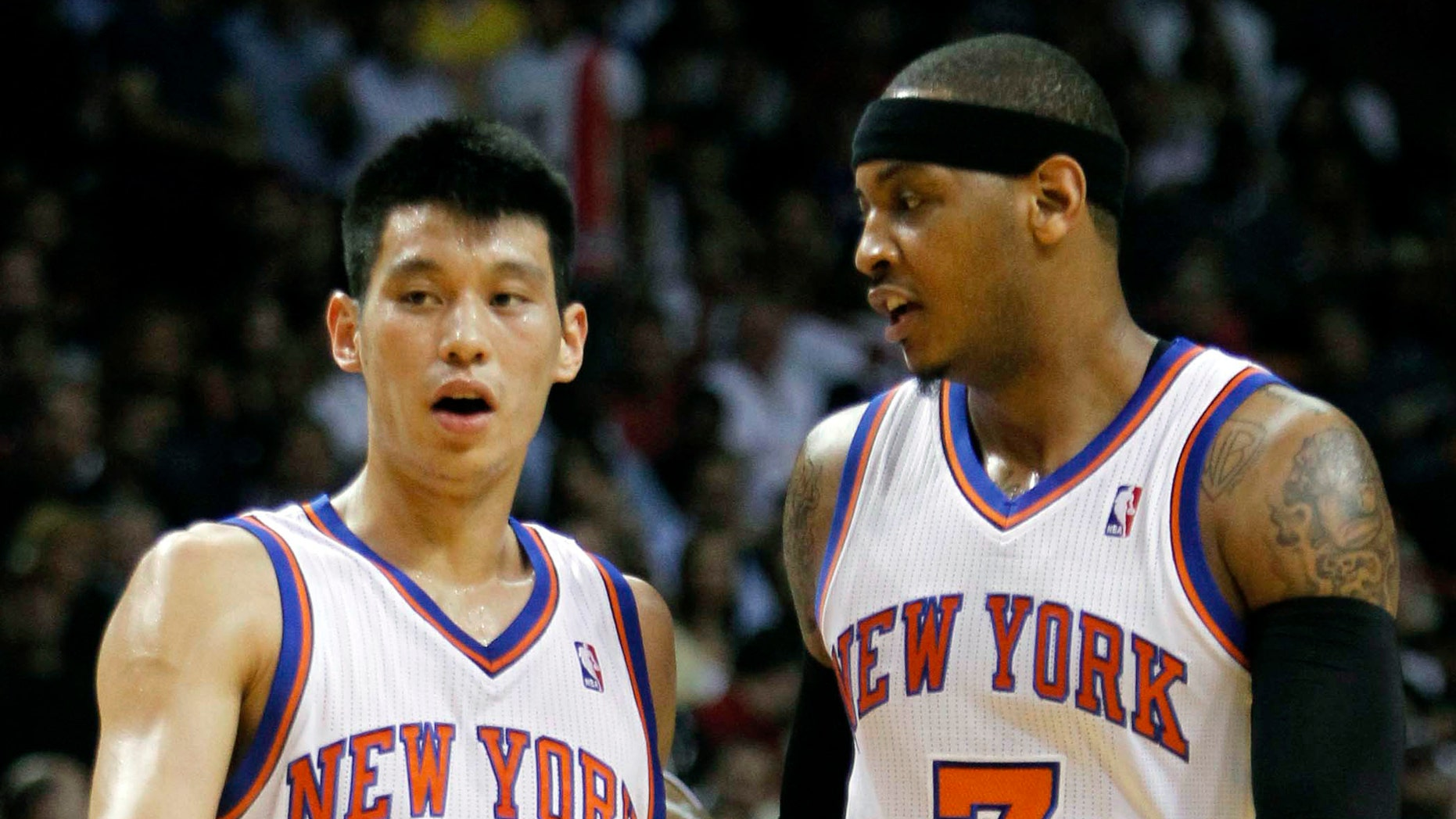 New York Knicks guard Jeremy Lin (17) and teammate Carmelo Anthony (7) talk during the first half of an NBA basketball game against the Miami Heat, Thursday, Feb. 23, 2012, in Miami.  (AP Photo/Alan Diaz)