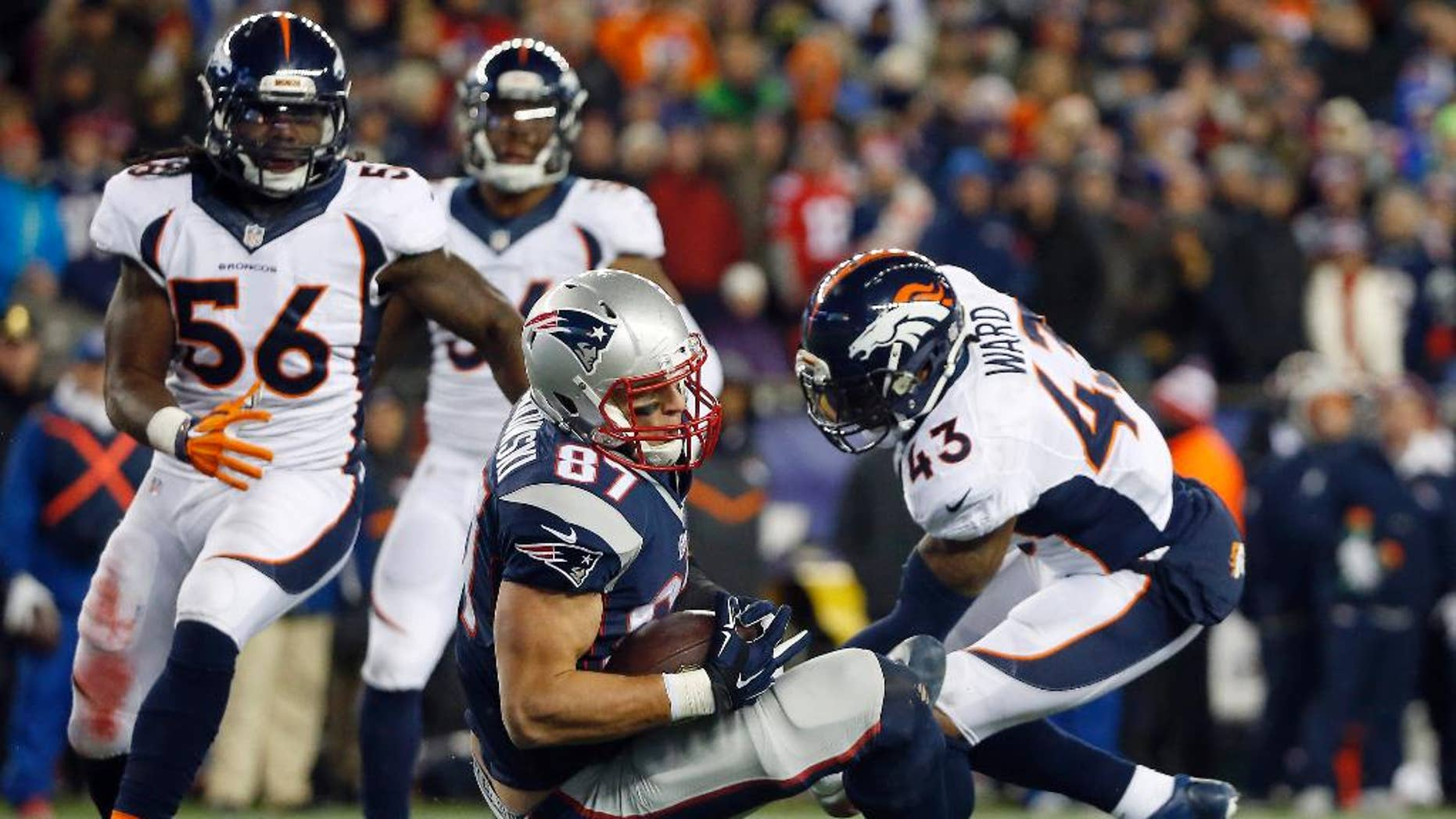 "FILE - In this Nov. 2, 2014, file photo, New England Patriots tight end Rob Gronkowski (87) lands between Denver Broncos middle linebacker Nate Irving (56) and strong safety T.J. Ward (43) after catching a pass in the fourth quarter of an NFL football game in Foxborough, Mass. Gronkowski's leaping, full-extension, one-handed, lefty grab of a pass from Tom Brady against the Broncos made perfectly clear that the man known as ""Gronk"" is back among the NFL's elite after a series of operations to his left forearm, his right knee and his back. (AP Photo/Elise Amendola, File)"