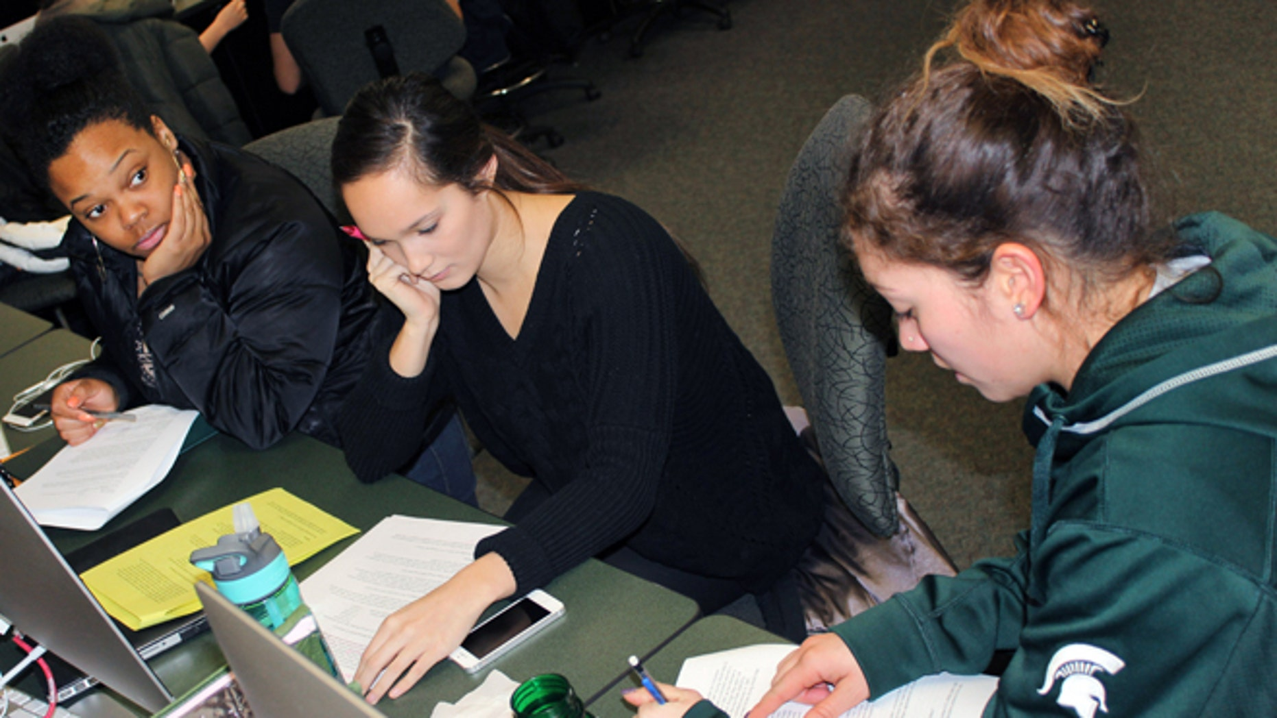 In this March 1, 2015 photo released by Joe Grimm, Michigan State University students Tiara Jones, from left, Madeline Carino and Lia Kamana work on a new book â100 Questions and Answers About Veteransâ in East Lansing, Mich. The new book, researched and written by a Michigan State journalism class with assistance from former servicemen and women, is aimed at clearing up myths and misunderstandings held by some civilians.  (AP Photo/Joe Grimm)