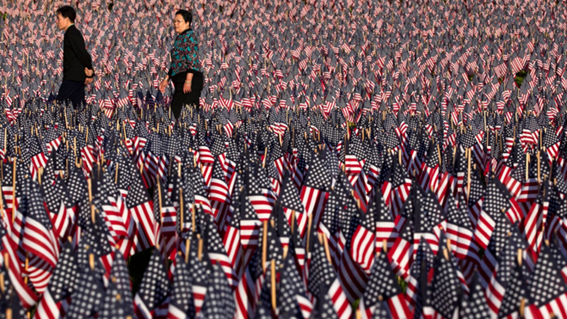 May 23, 2012: People walk through a portion of the Boston Common covered with American flags. Relatives and volunteers planted the 33,000 flags in the historic park in advance of the Memorial Day weekend, in tribute to Massachusetts soldiers killed in conflicts as far back as the Civil War.