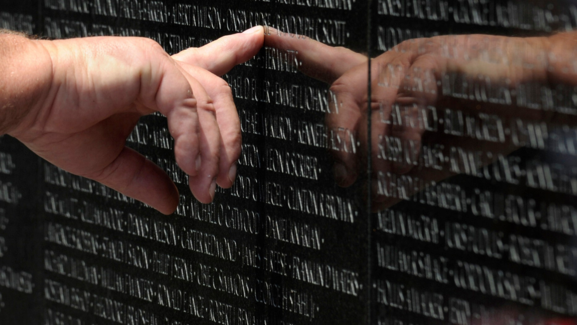 A visitor to the Vietnam Veteran's Memorial touches the name of a fallen soldier etched on the wall of the memorial in Washington, Friday, May 25, 2012. On Monday, the Vietnam Veterans Memorial Wall will begin the national commemoration of the Vietnam Warâs 50th anniversary. (AP Photo/Susan Walsh)