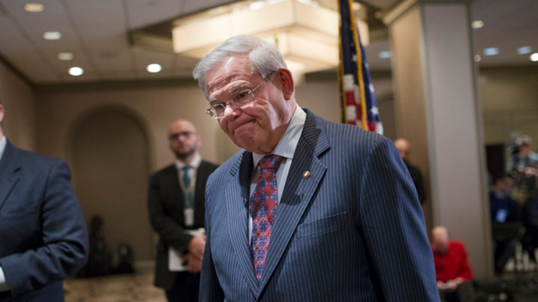 Sen. Bob Menendez, D-N.J., leaves after news conference in Newark, N.J. on Friday, March 6, 2015. A person familiar with a federal investigation says the Justice Department is expected to bring criminal charges against the New Jersey Democrat in the coming weeks. Menendez says that he has always behaved appropriately in office. (AP Photo/John Minchillo)