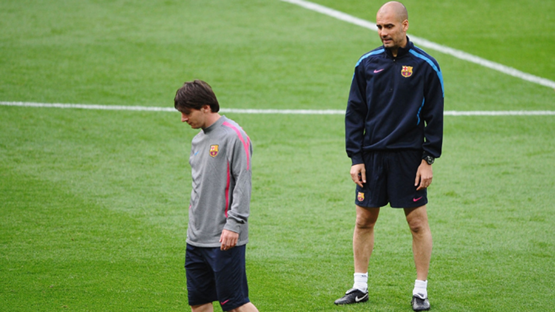 """Lionel Messi of FC Barcelona (L) walks away from Josep """"Pep"""" Guardiola, then-manager of FC Barcelona looks on during training session at Wembley Stadium in London on May 27, 2011. The two will face off in a game between Barca and Guardiola's new team, Bayern Munich. (Photo by Laurence Griffiths/Getty Images)"""