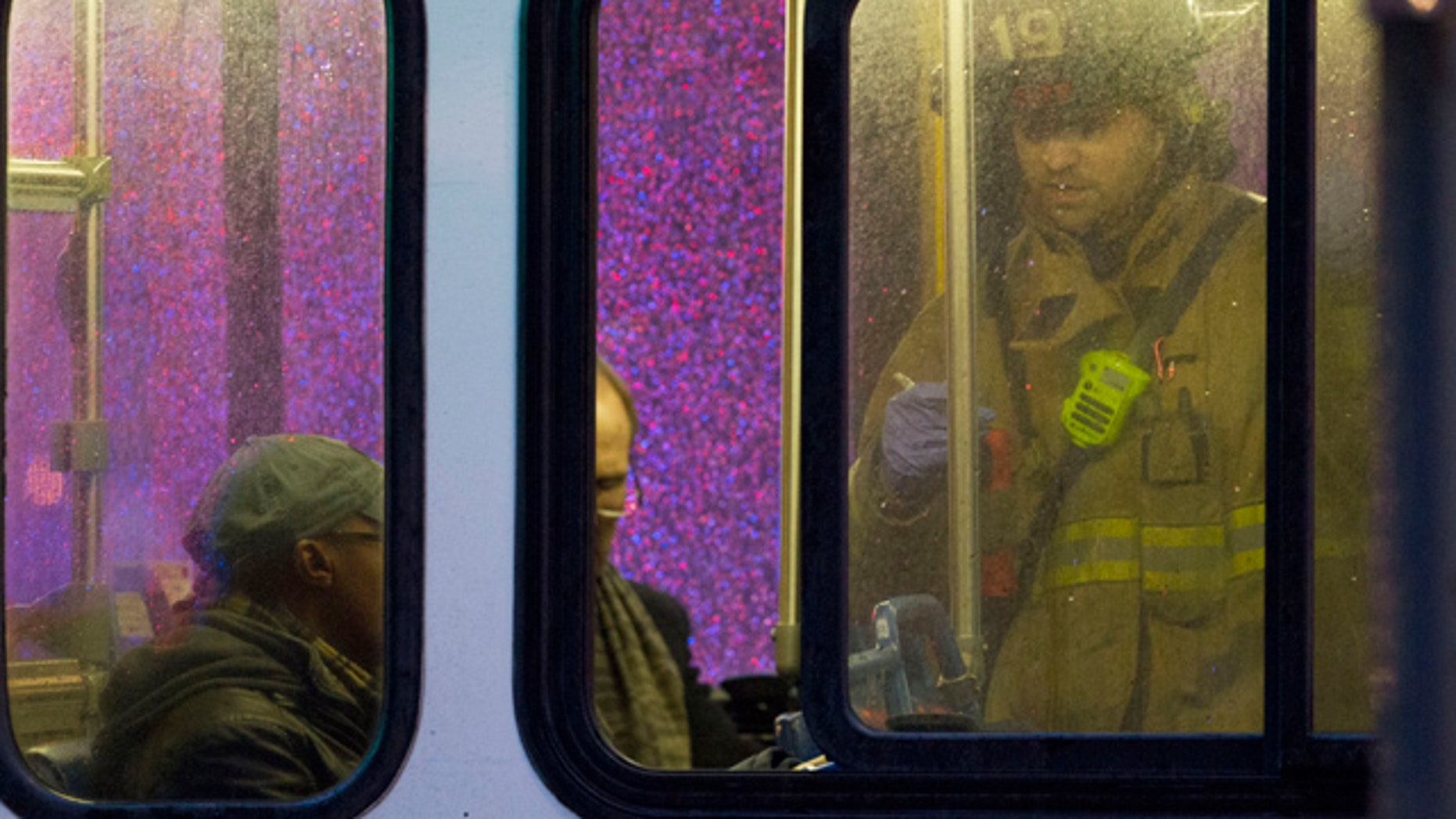 FILE - In this Jan. 12, 2015, file photo, a firefighter attends people on a bus to assess triage needs after people were evacuated from a smoke-filled Metro subway tunnel in Washington. One woman died and more than 80 others were sickened by smoke after an electrical malfunction in January caused a train to fill with smoke while it stopped in a tunnel in downtown Washington.  (AP Photo/Jacquelyn Martin, File)
