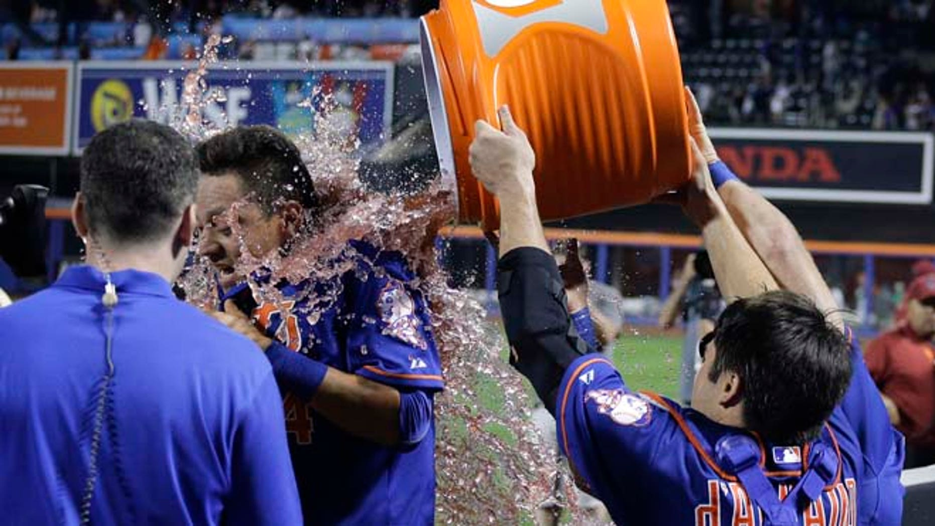 New York Mets' Wilmer Flores is doused by teammate Travis d' Arnaud and Kevin Plawecki after hitting a walk-off solo home run in the 1th inning of a baseball game to beat the Washington Nationals 2-1.