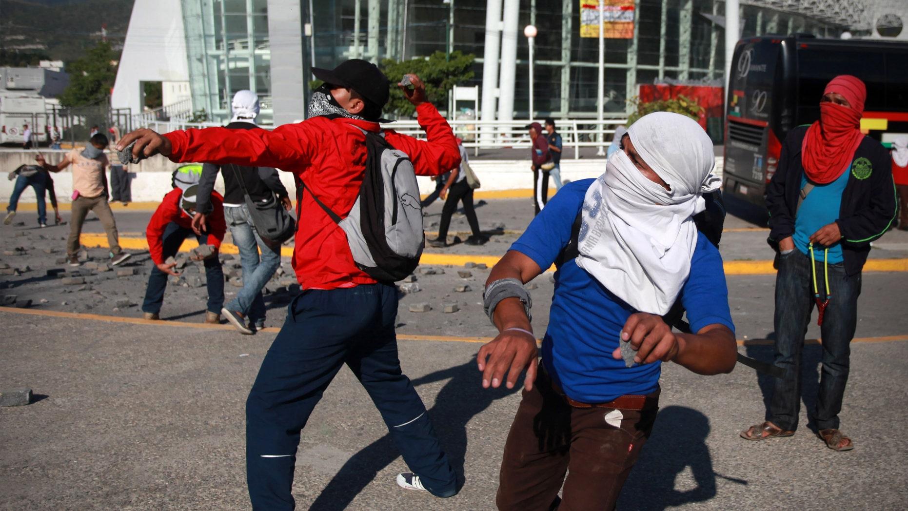 Estudiantes arrojan piedras al palacio de gobierno en Chilpancingo, capital del estado de Guerrero, México, lunes 13 de octubre de 2014. Violentas protestas con lanzamiento de cócteles molotov contra edificios gubernamentales, algunos de los cuales sufrieron daños, se vivieron el lunes en el estado del sur de México donde un estudiante alemán fue baleado por la policía aparentemente por confusión la noche anterior y donde hace dos semanas desaparecieron 43 estudiantes, presuntamente a manos de la policía.  (AP Foto/Felix Marquez)College students throw rocks as they trash and later set on fire the state capital building in Chilpancingo, Mexico, Monday Oct. 13, 2014. Hundreds of protesting teachers and students demanding answers about the 43 students who went missing on Sept. 26 during a confrontation with police, clashed with police at the local congress and outside the state government palace Monday. Officials are attempting to determine if any of the missing students are in newly discovered mass graves. (AP Photo/Felix Marquez)