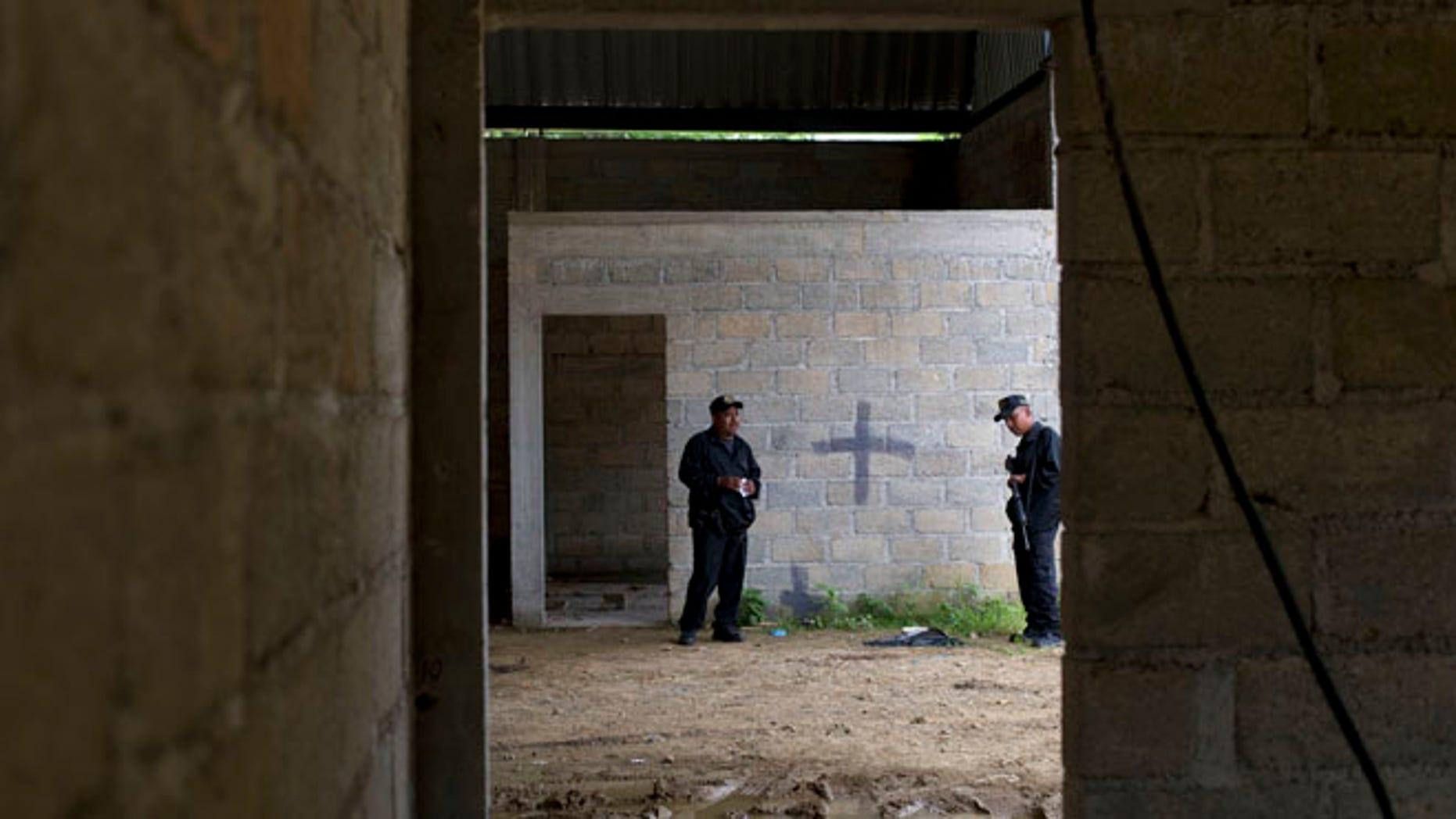 FILE - In this July 3, 2014 file photo, state police stand inside a warehouse where a black cross marks a wall near blood stains on the ground, after a shootout between Mexican soldiers and alleged criminals in Tlatlaya, Mexico. A Mexican civilian court has freed the final three soldiers accused of homicide in the 2014 incident in which suspects were allegedly executed after they surrendered. The federal Attorney Generalâs Office said late Friday, May 13, 2014, the three were absolved of charges of homicide, cover-up and alteration of evidence. (AP Photo/Rebecca Blackwell, File)