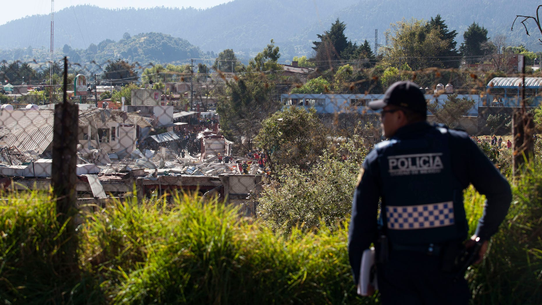 MEXICO CITY, MEXICO - JANUARY 29:  A police officer stands guard as search and rescue workers inspect the rubble of an explosion at a children's hospital on January 29, 2015 in Mexico City, Mexico. Officials believe the explosion was caused by a leak from a gas truck. At least four people were killed and dozens injured. (Photo by Brett Gundlock/Getty Images)