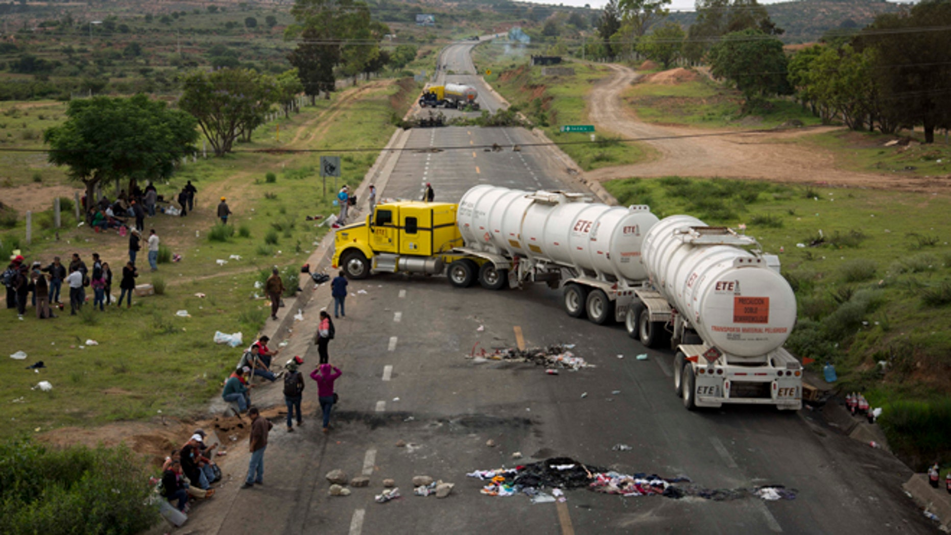 Protesters stand beside trucks blocking the highway in the state of Oaxaca, near the town of Nochixtlan, Mexico, Monday, June 20, 2016. Mexican police say few teachers were involved in violence at a weekend highway protest in the southern state of Oaxaca in which six people died. The teachers are protesting against plans to overhaul the country's education system which include federally mandated teacher evaluations. (AP Photo/Eduardo Verdugo)