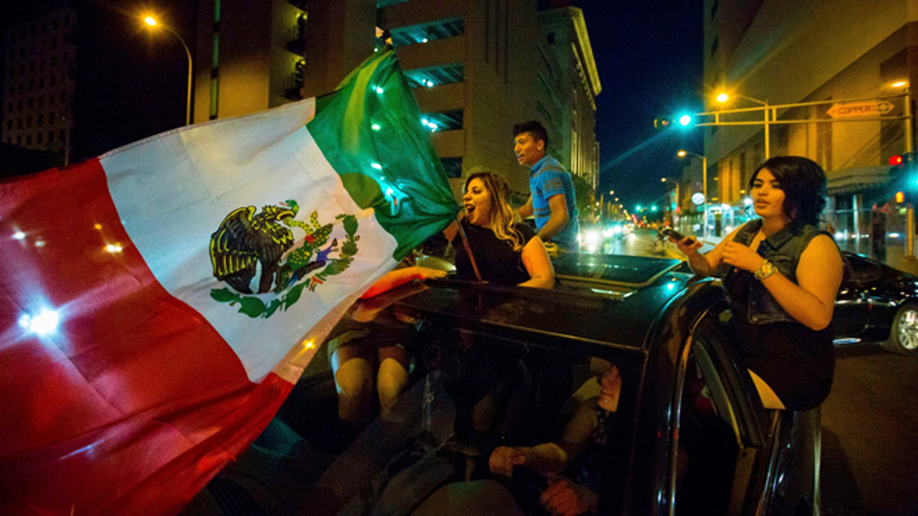 File - In this May 24, 2016, file photo, a woman waves the Mexican flag while driving past the Albuquerque Convention Center after a rally by Republican presidential candidate Donald Trump in Albuquerque, N.M. It's a flag seen at many protests against presumptive Republican presidential nominee Donald Trump. It also can be spotted at immigration rallies, on murals in cities with sizeable Latino populations and at Mexican National team soccer games held on U.S. soil. The flag of Mexico has a long history in the United States, despite being a symbol of a nation south of the border. (Jett Loe/The Las Cruces Sun-News via AP, File) MANDATORY