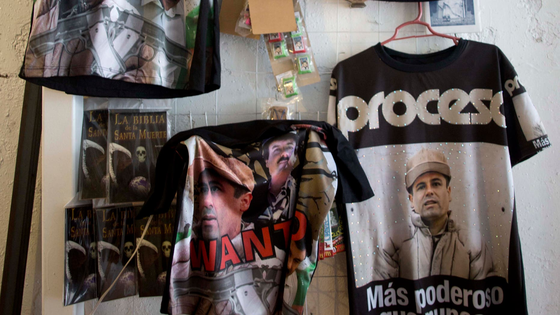 "T-shirts featuring fugitive Mexican drug lord Joaquín ""El Chapo"" Guzmán hang for sale inside the shrine of a faith healer in Mexico City, Friday, Oct. 16, 2015. The government is offering a reward of 60 million pesos, or about $3.5 million dollars, for Guzmán's recapture after he made his second escape from a maximum security prison through an underground tunnel in 2015. (AP Photo/Eduardo Verdugo)"