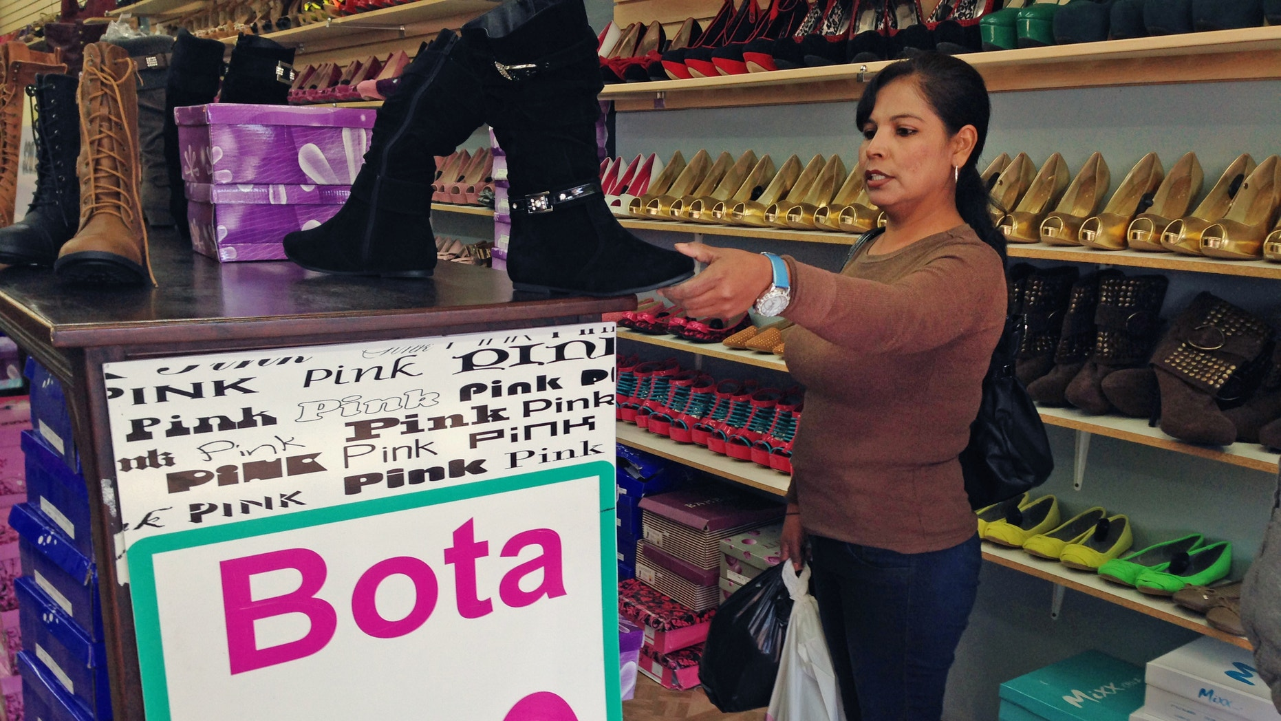 In this Dec. 19, 2014 photo, Martha Isabel Velasquez looks at a pair of boots while shopping in downtown Nogales, Ariz. Velasquez says she waited two hours in line to cross by foot over from Nogales, Sonora, Mexico, to go shopping. She said weak peso left her cash strapped and that she wouldnt be able to buy as much. Border communities drive the economy in border towns such as Nogales, but a recent drop in the value of the peso and long lines at ports of entry have caused a decrease in shoppers. (AP Photo/Astrid Galvan)