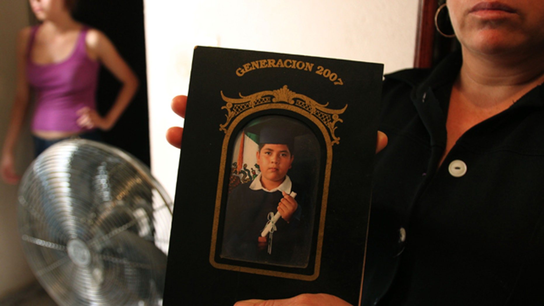 A family member holds a photograph of Alejandro Leon Castellanos, 15, who died when soldiers opened fire on the family vehicle.