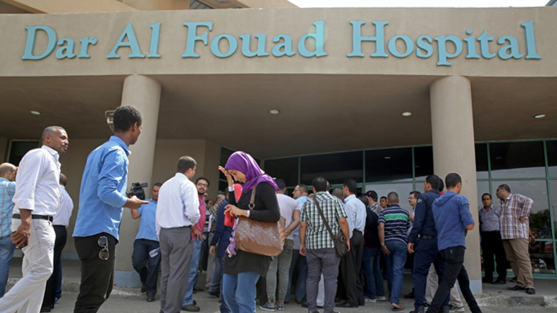 Egyptian journalists wait for information about tourists who were injured Sunday while on a desert safari trip, in front of the Dar Al Fouad Hospital in Cairo, Egypt, Monday, Sept. 14, 2015. At least 12 people were killed and 10 injured in Egypt's southwestern desert Sunday, Sept 13, 2015, when security forces mistakenly fired on a group of Mexican tourists, Egyptian officials said. The Mexican Foreign Ministry confirmed the incident and said at least two of the dead were Mexican nationals. (AP Photo/Nariman El-Mofty)