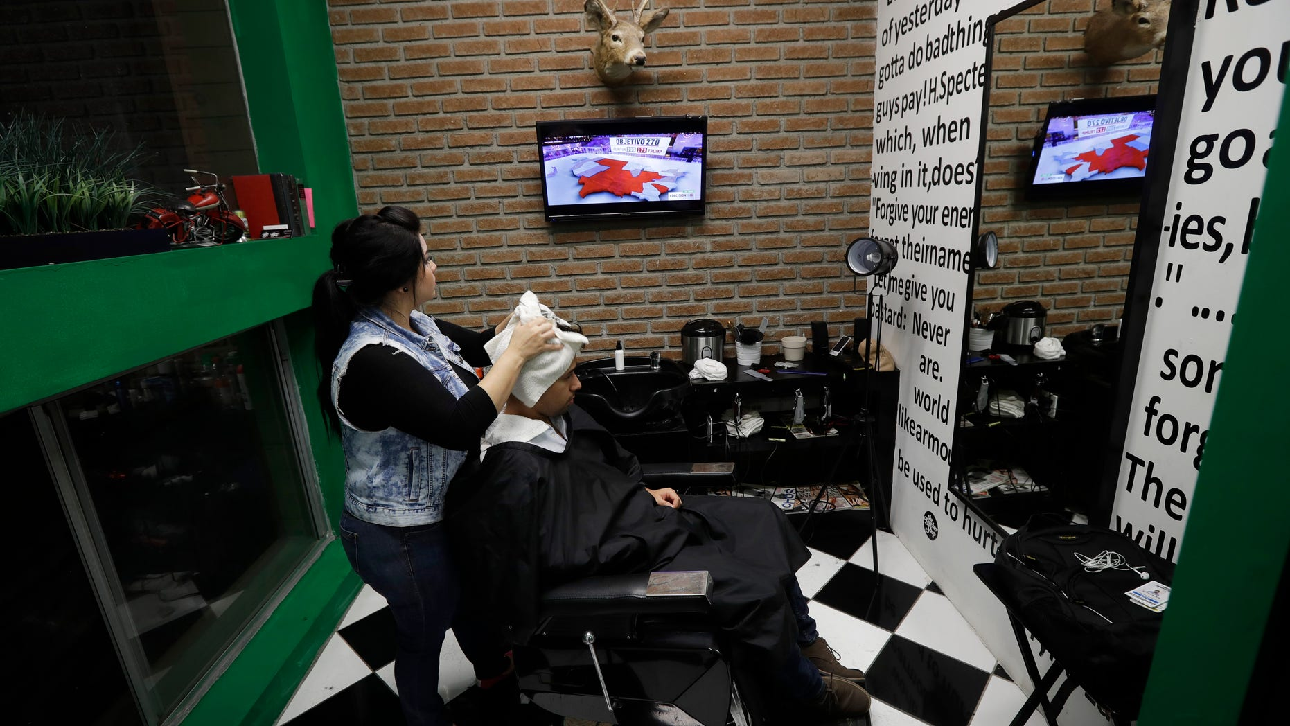 Paula Noriega, left, looks up at a screen displaying news of the elections in the United States as she dries the hair of Alan Maldonado at a barber shop Tuesday, Nov. 8, 2016, in Tijuana, Mexico. (AP Photo/Gregory Bull)