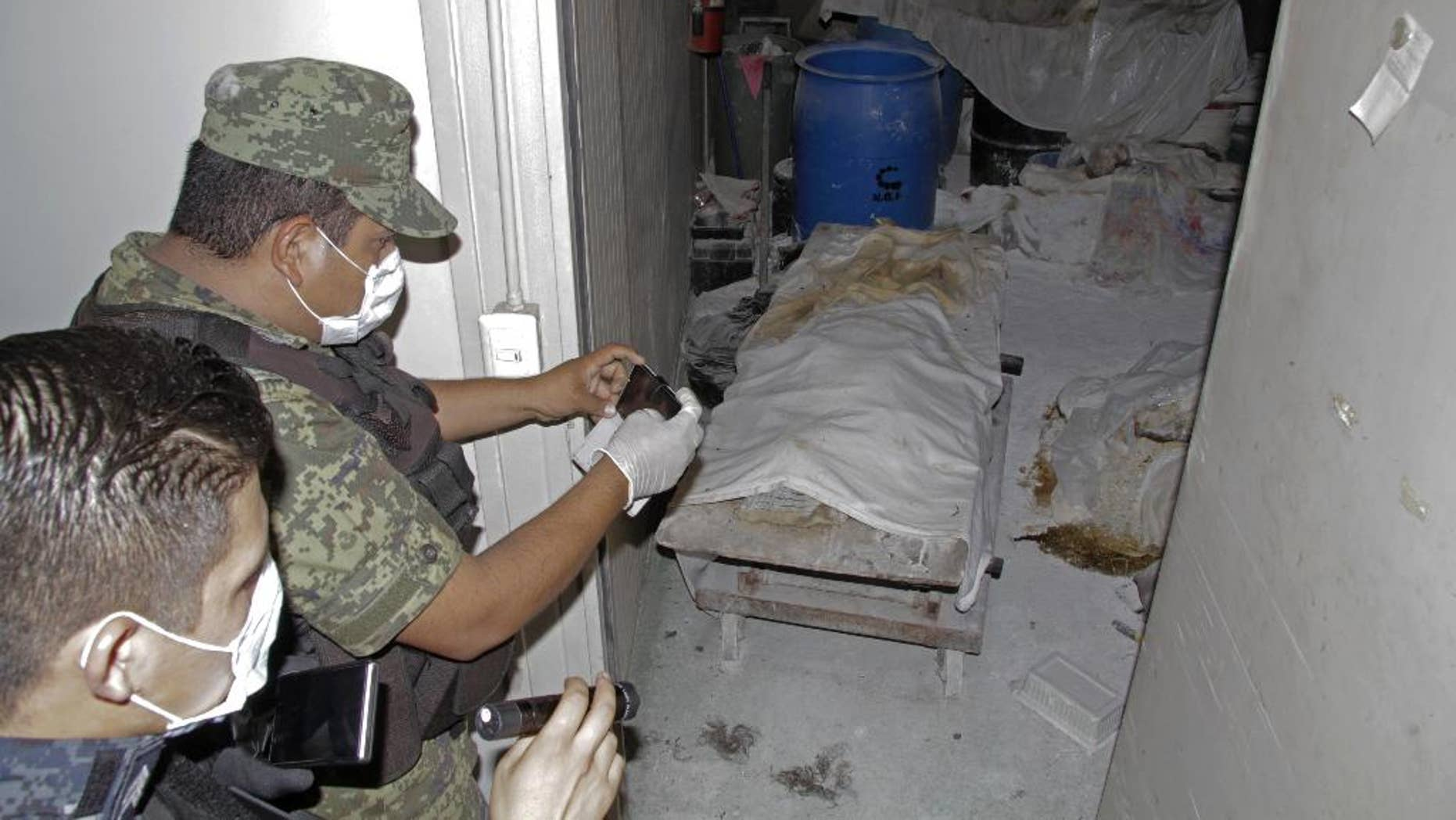 Feb. 6, 2015 - A Mexican army soldier takes photos of a room full of bodies covered with sheets at the crematorium of an abandoned funeral home near Acapulco, Mexico. 61 rotting bodies were discovered Thursday evening at the facility, which had been shuttered for about a year, according to a government official.