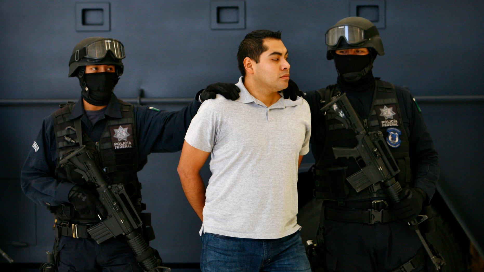 July 15, 2012: Suspect Bogard Felipe Lugo de Leon, center, is escorted by police officers during his presentation to the media in Mexico City.