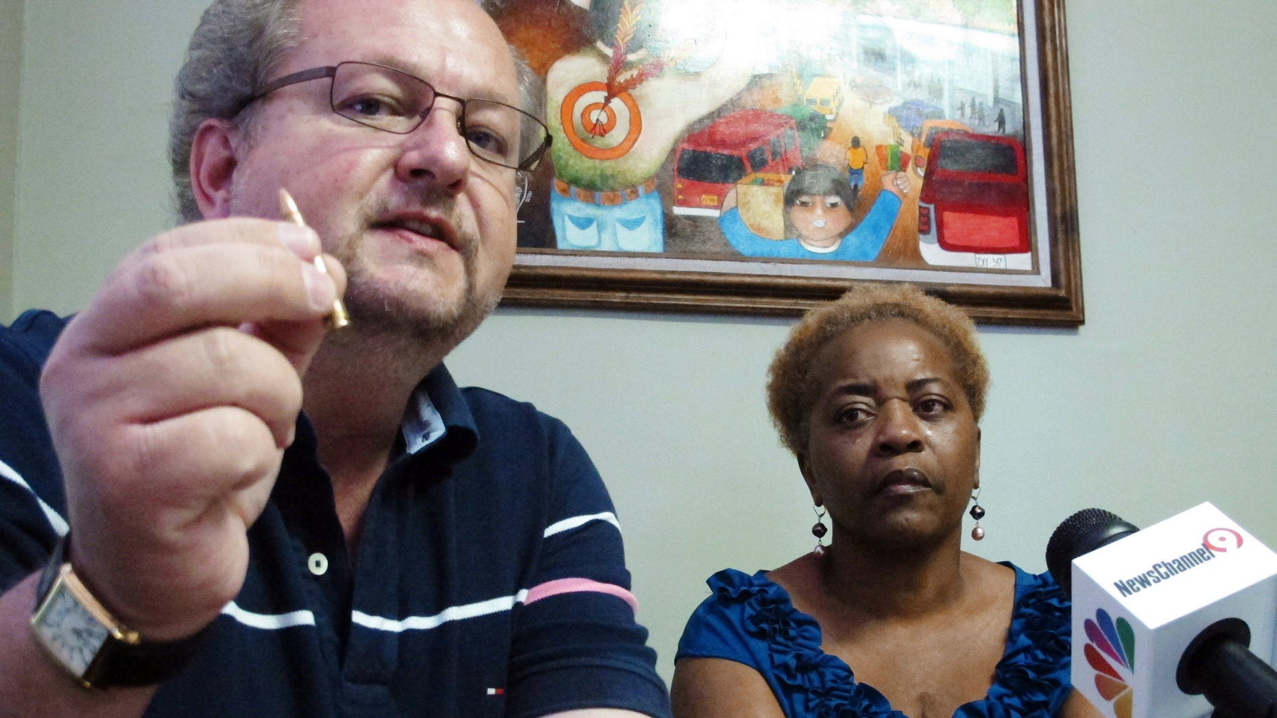 Kevin Huckabee, left, who also claims his son was wrongfully arrested in Mexico, holds a bullet as Aletha Smith, mother of trucker Jabin Bogan looks on during a news conference, Wednesday, May 2, 2012 in El Paso, Texas. Bogan, who was arrested with 268,000 bullets in Mexico, claims he took a wrong turn that led him into Mexico while transporting the cargo for an ammunition dealer in Arizona. (AP Photo/Juan Carlos Llorca)
