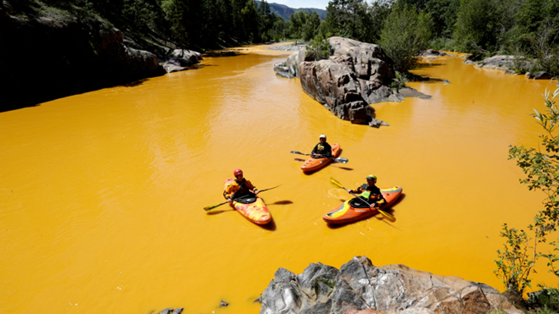 In this Thursday, Aug. 6, 2015 file photo, people kayak in the Animas River near Durango, Colo., in water colored yellow from a mine waste spill. A crew supervised by the U.S. Environmental Protection Agency has been blamed for causing the spill while attempting to clean up the area near the abandoned Gold King Mine. Tribal officials with the Navajo Nation declared an emergency on Monday, Aug. 10, as the massive plume of contaminated wastewater flowed down the San Juan River toward Lake Powell in Utah, which supplies much of the water to the Southwest. (Jerry McBride/The Durango Herald via AP, FILE)