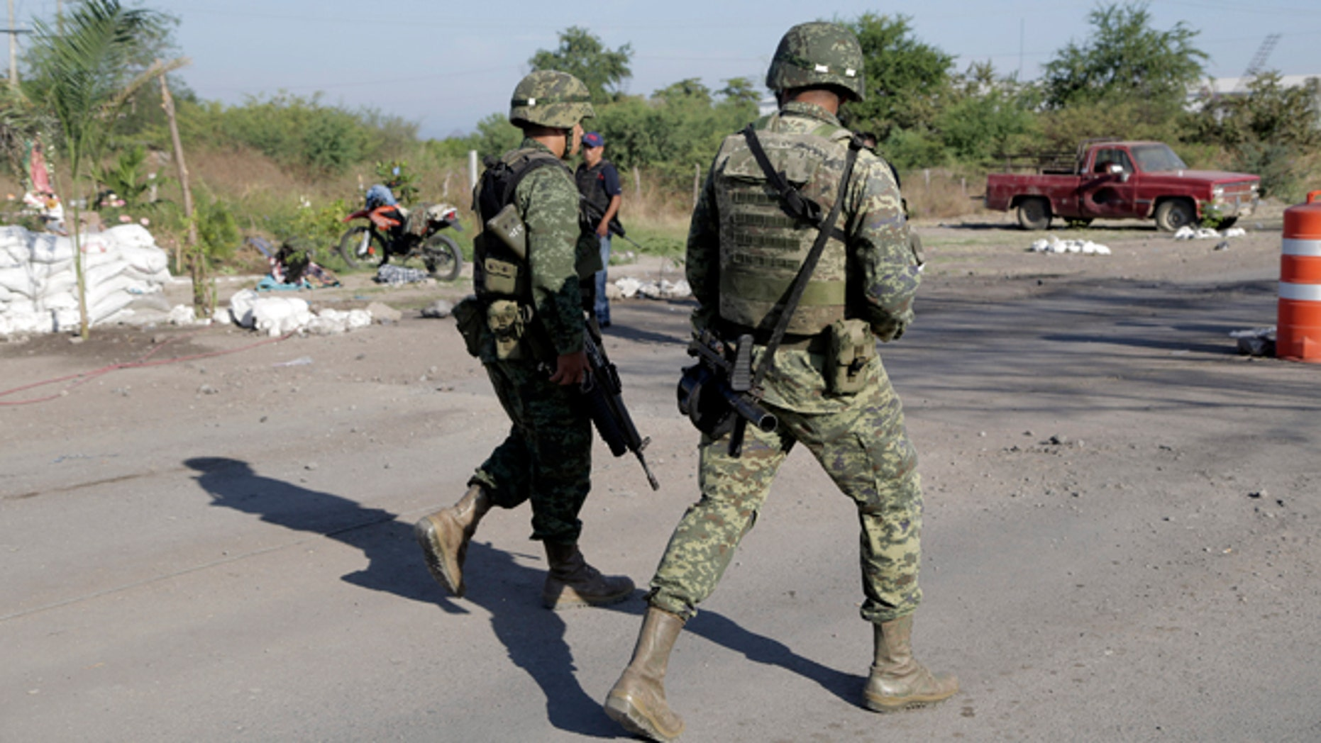 "Mexican army soldiers walk at the entrance into the town of La Ruana a day after a clash between two rival ""self-defense"" groups outside of the town, in the state of Guerrero, Mexico, Wednesday Dec. 17, 2014. According to federal authorities, both groups fought at a barricade at the entrance to the community resulting in several dead on both sides. (AP Photo/Gustavo Aguado)"