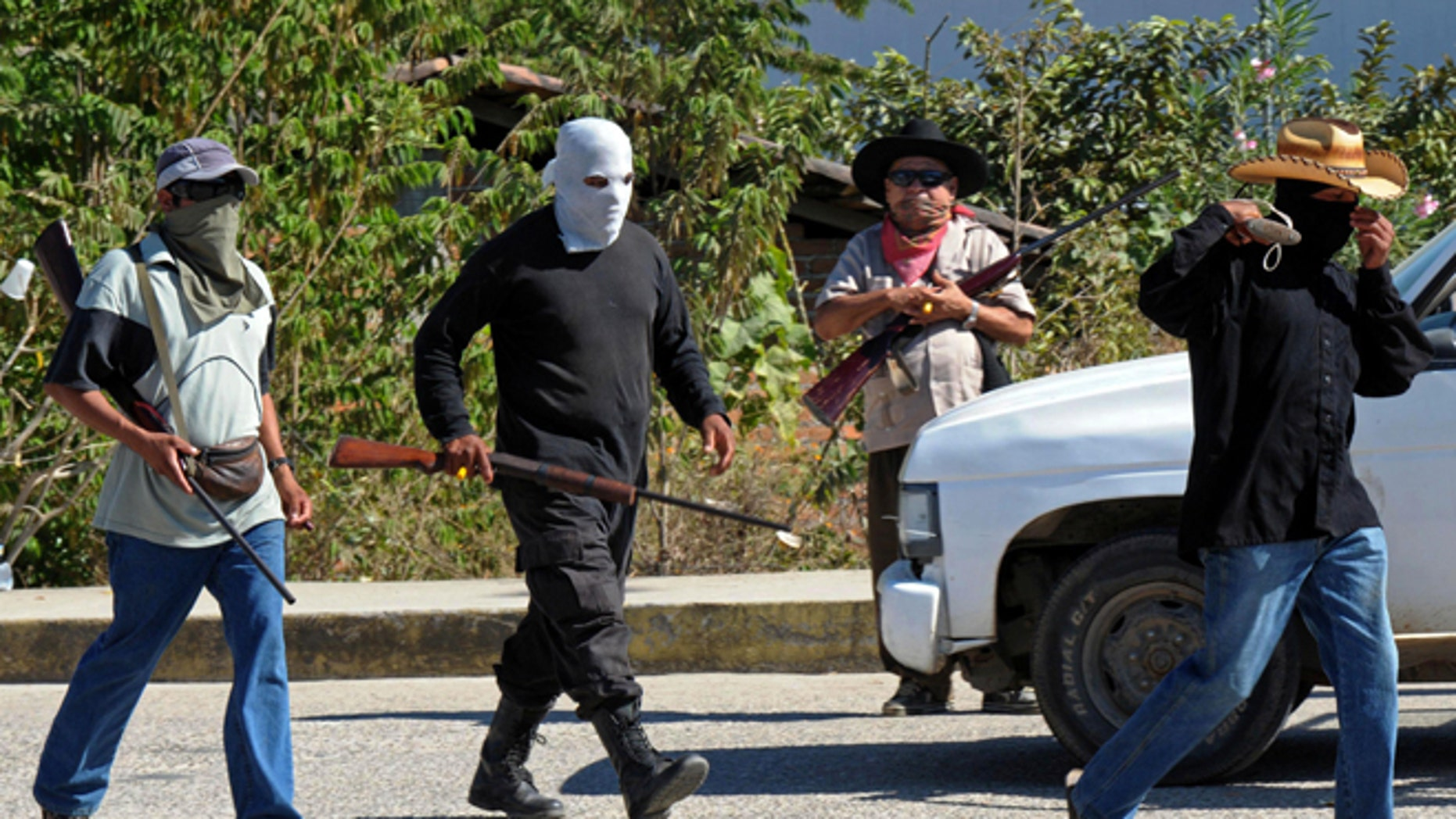 Civilians wearing ski masks or bandanas and carrying small arms, man a checkpoint in Teconoapa, in the Mexican state of Guerrero, Friday, Jan. 11, 2013. Several hundred civilians have taken up arms in two towns in the southwestern Mexico state and are arresting people suspected of crimes and imposing a curfew. Leaders said they were acting against crime and insecurity. Guerrero Gov. Angel Aguirre Rivero responded Friday by announcing that security in the region would be bolstered by sending in Mexican soldiers and marines and federal and state police officers. (AP Photo/Bernandino Hernandez)