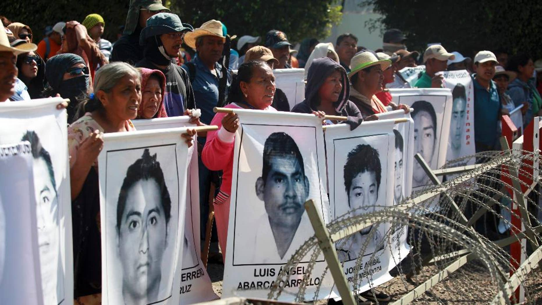FILE - In this Dec. 18, 2014 file photo, relatives of missing students protest in front of the entrance to the 27th Infantry Battalion base in Iguala, Mexico. Mexican authorities announced Tuesday, Jan. 13, 2015, that the parents of the 43 missing students can enter army bases to search for their sons, but say there is no evidence the army was involved in their disappearance. (AP Photo/Felix Marquez, File)
