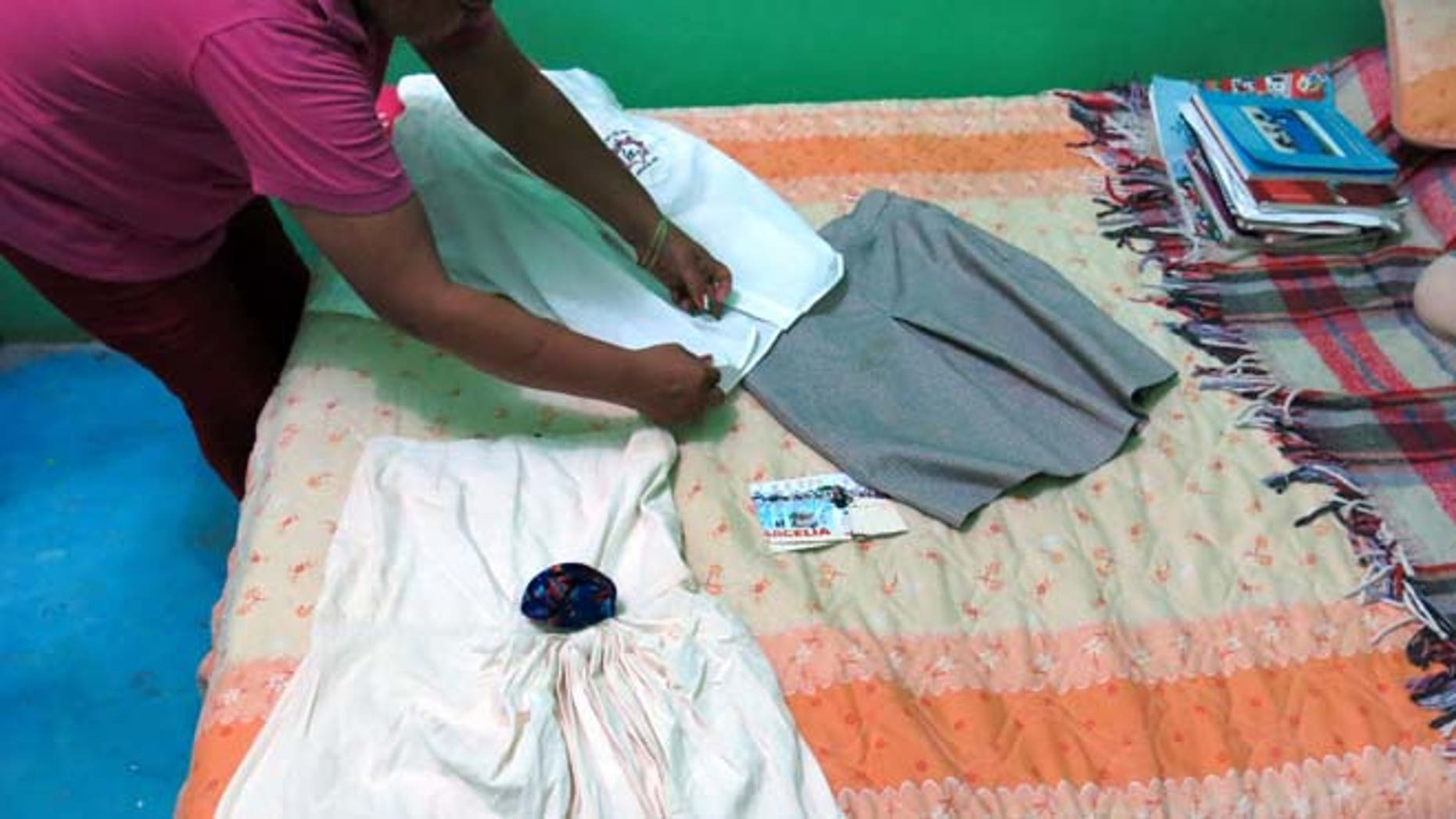 In this Sept. 15, 2014 photo, a woman who did not want to give her name for fear of reprisals, lays out the clothes of her late 15-year-old daughter Erika Gomez Gonzalez, on a bed at her home in Arcelia, Mexico. (AP)