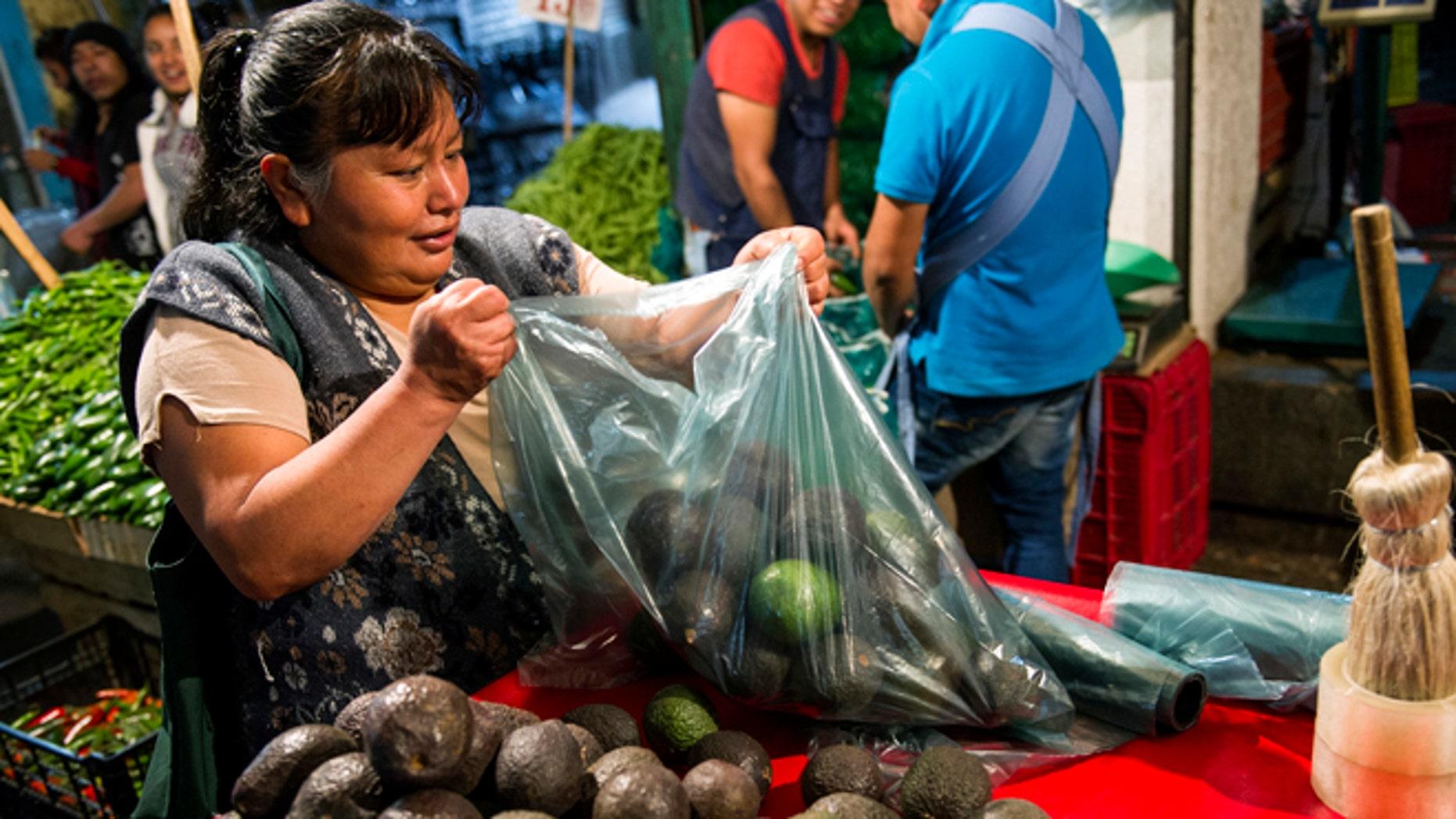 A woman prepares a bag of avocados in Mexico City, Tuesday, Aug. 9, 2016.